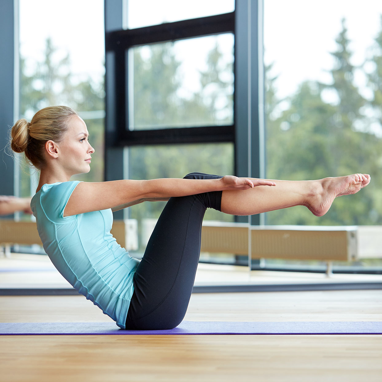 A woman holds a boat pose and focuses