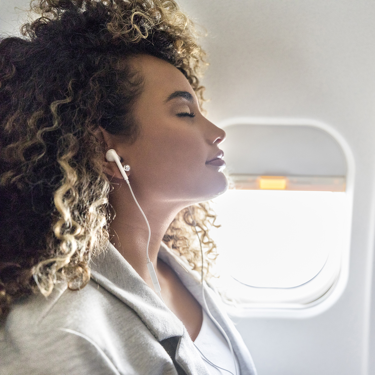 Attractive young woman closes her eyes while listening to music during a flight