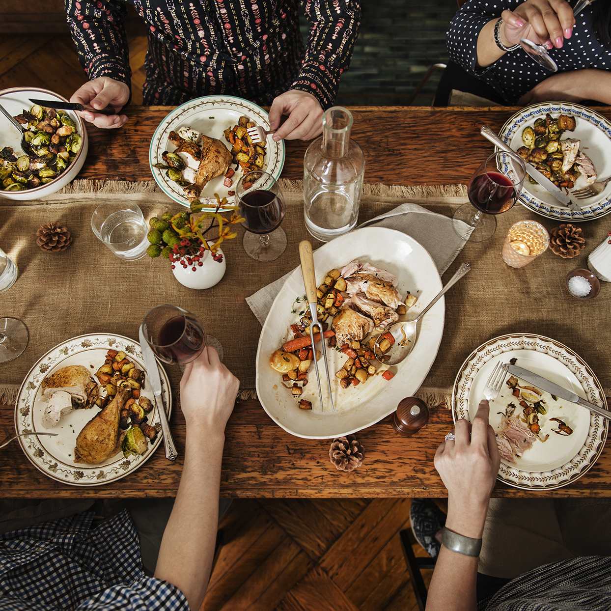 Group of people eating thanksgiving dinner with Turkey, red wine, Brussels sprouts and vegetables