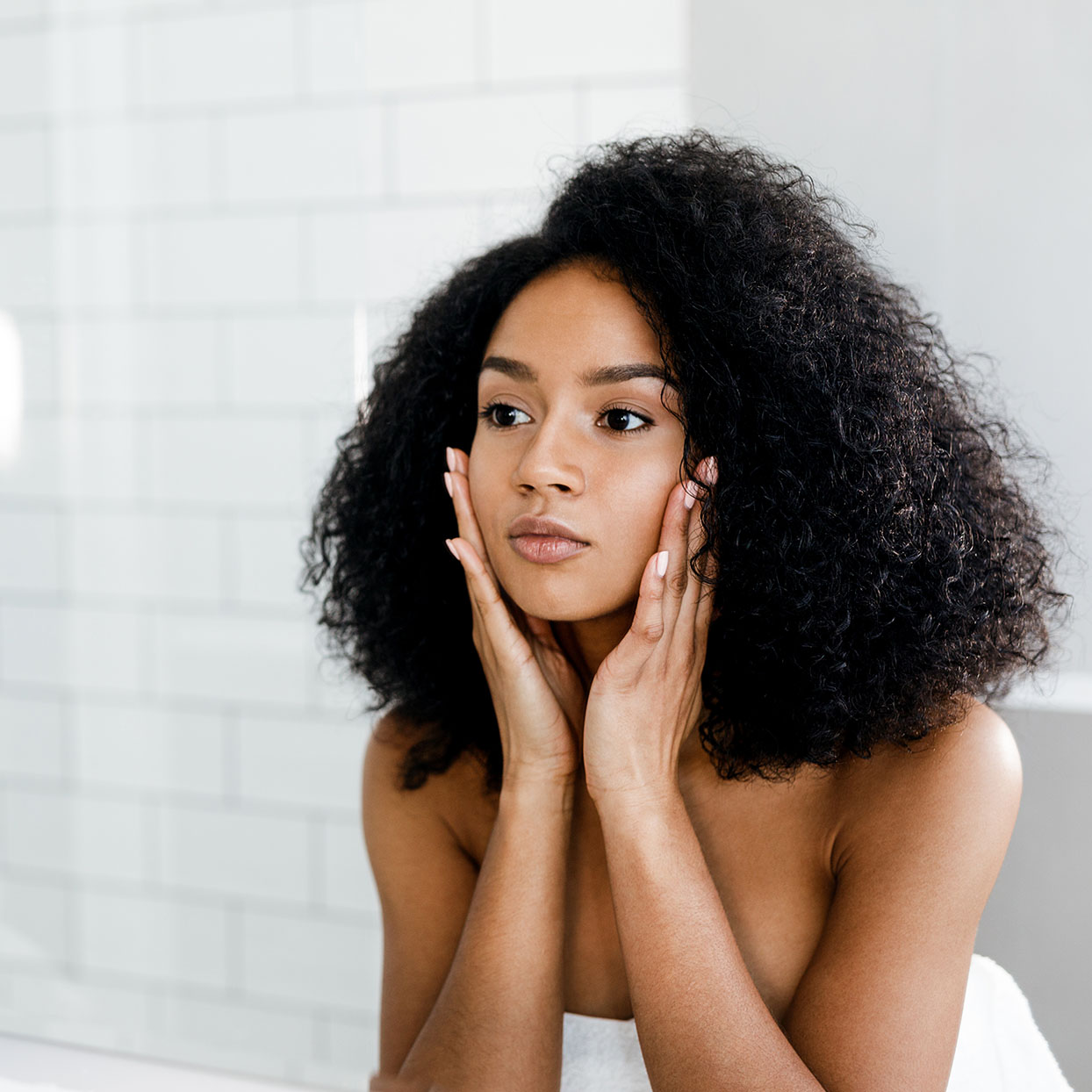 A woman smoothes her face in a mirror.