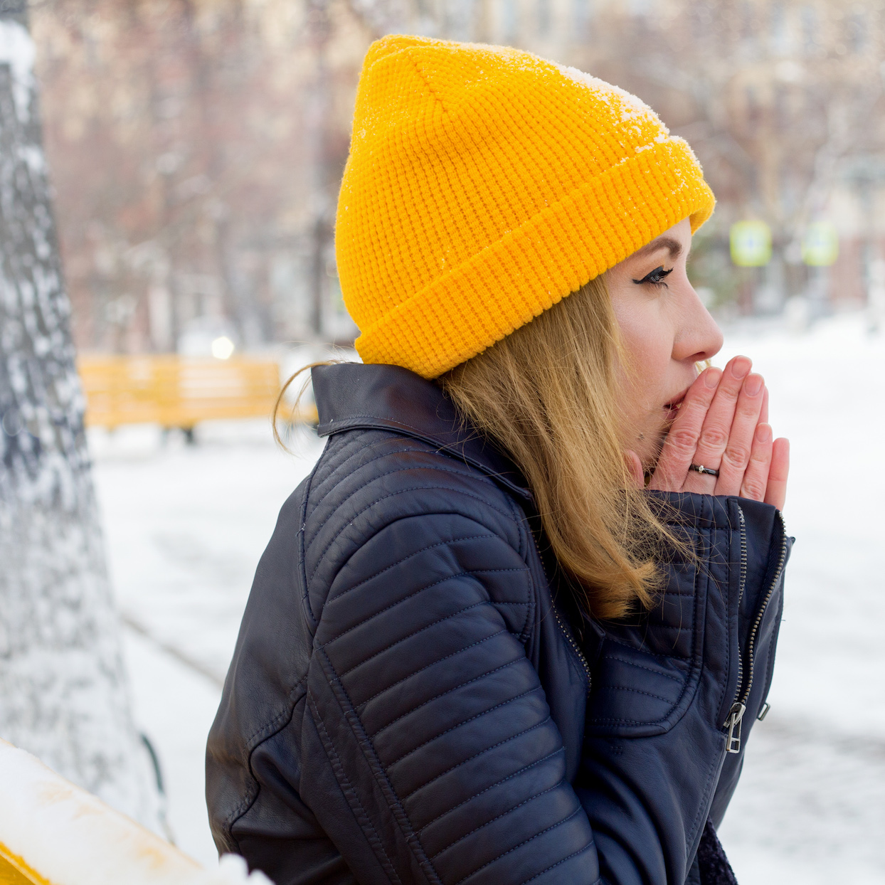 beautiful young woman warming her hands on the street in winter