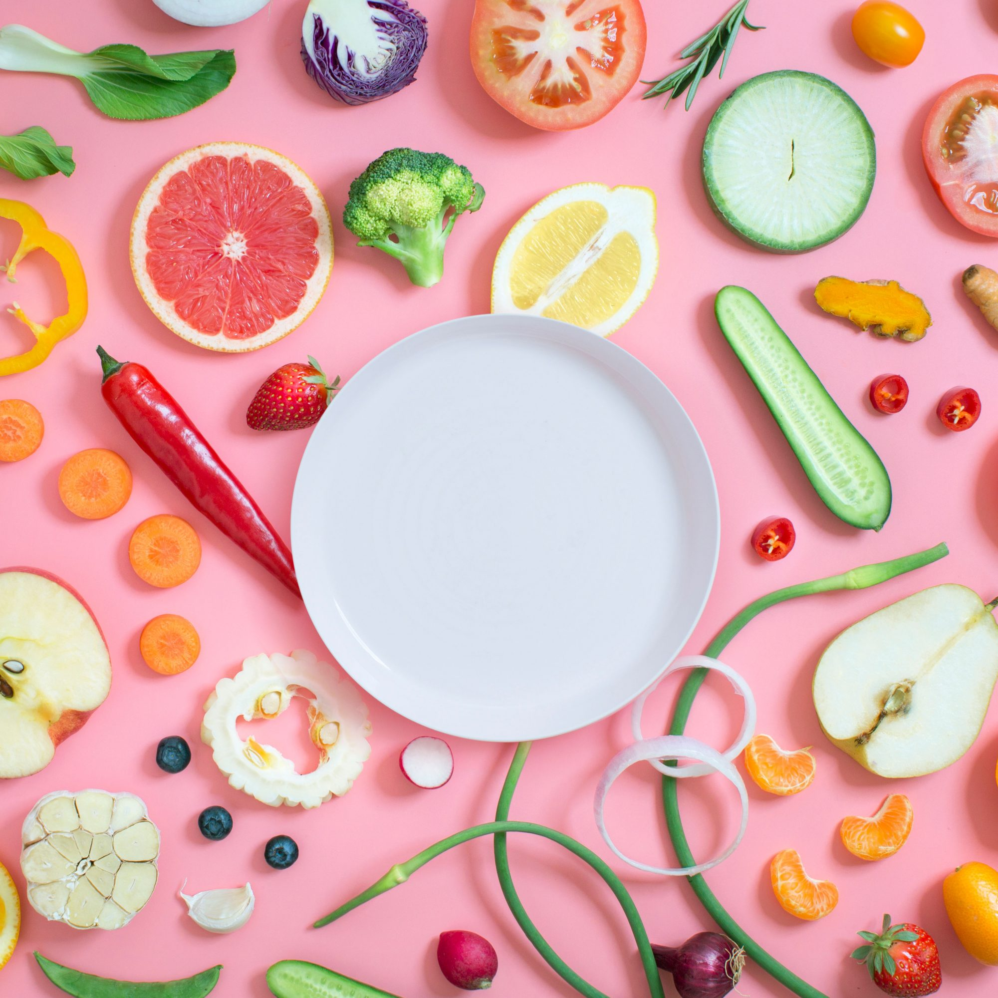 Colorful_Fruits_and_Vegetables_Scattered_Around_A_White_Plate
