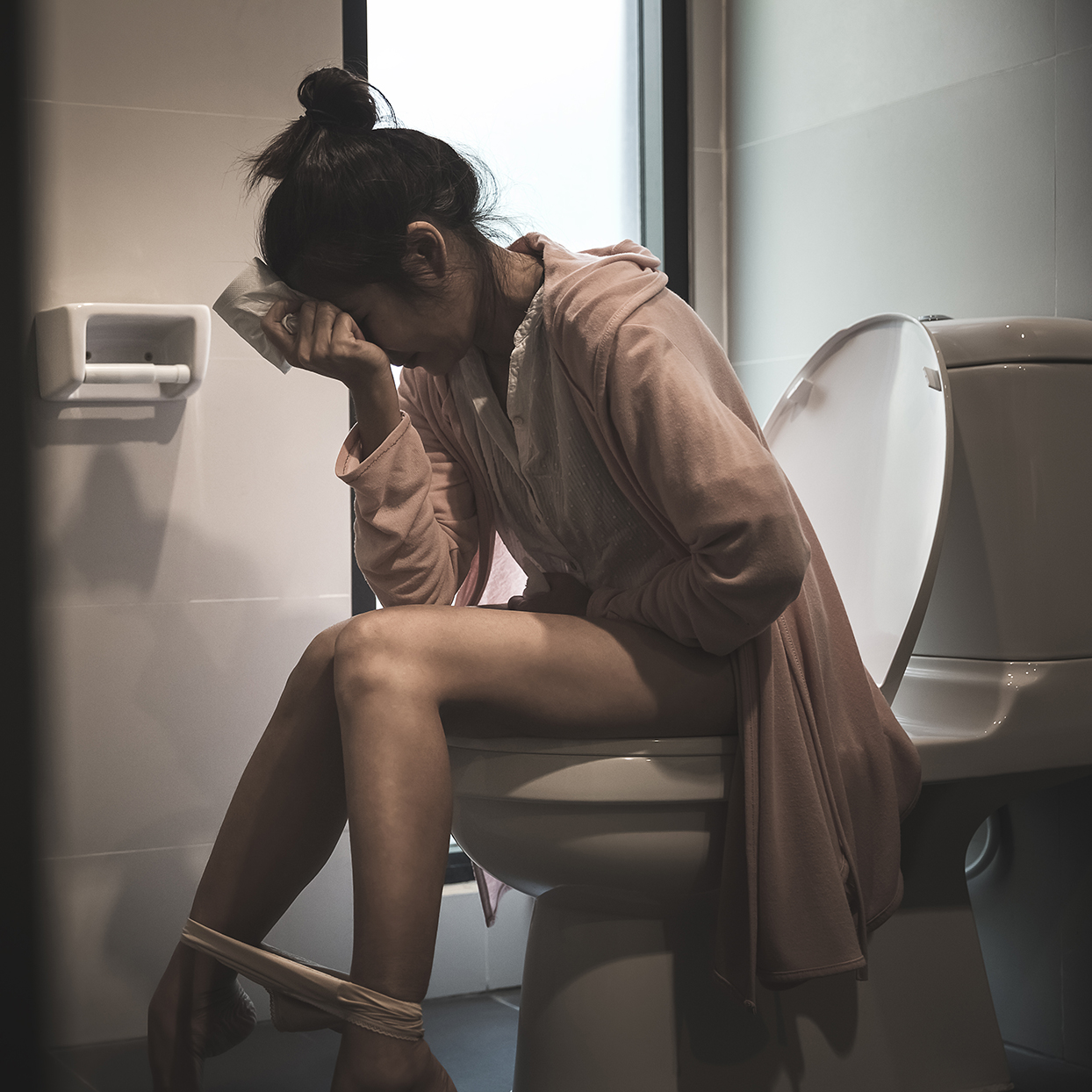 woman sitting on toilet bowl with stress gesture, health concept