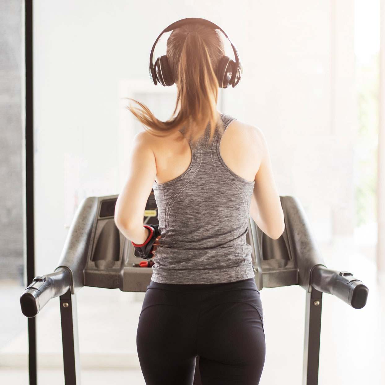 Rear View Of Woman Listening Music While Running On Treadmill At Gym 1244x1244