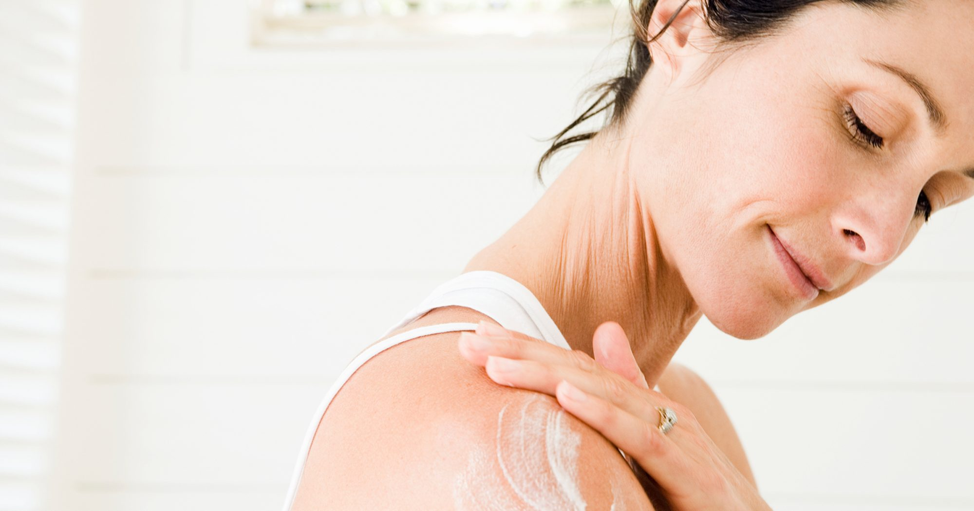 Woman Applying Lotion on Arm2370X1244