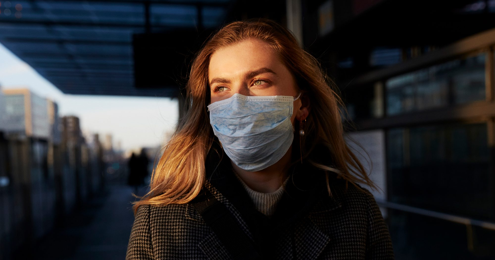 Young woman standing on train station wearing protective mask