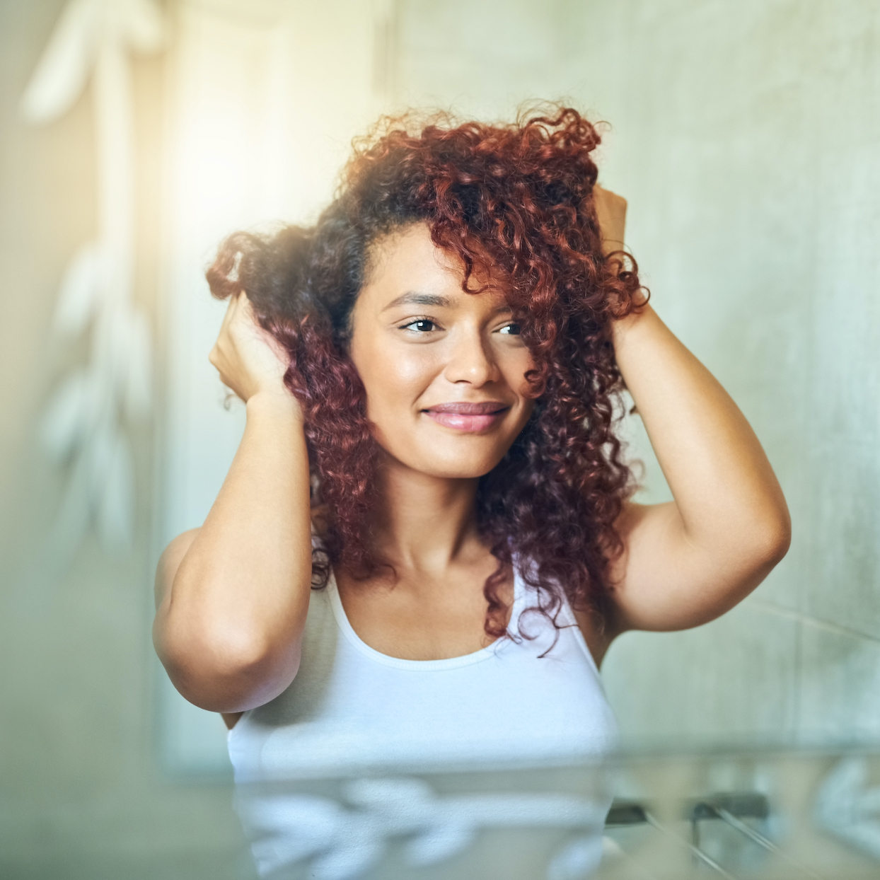 Shot of a young woman going through her haircare routine