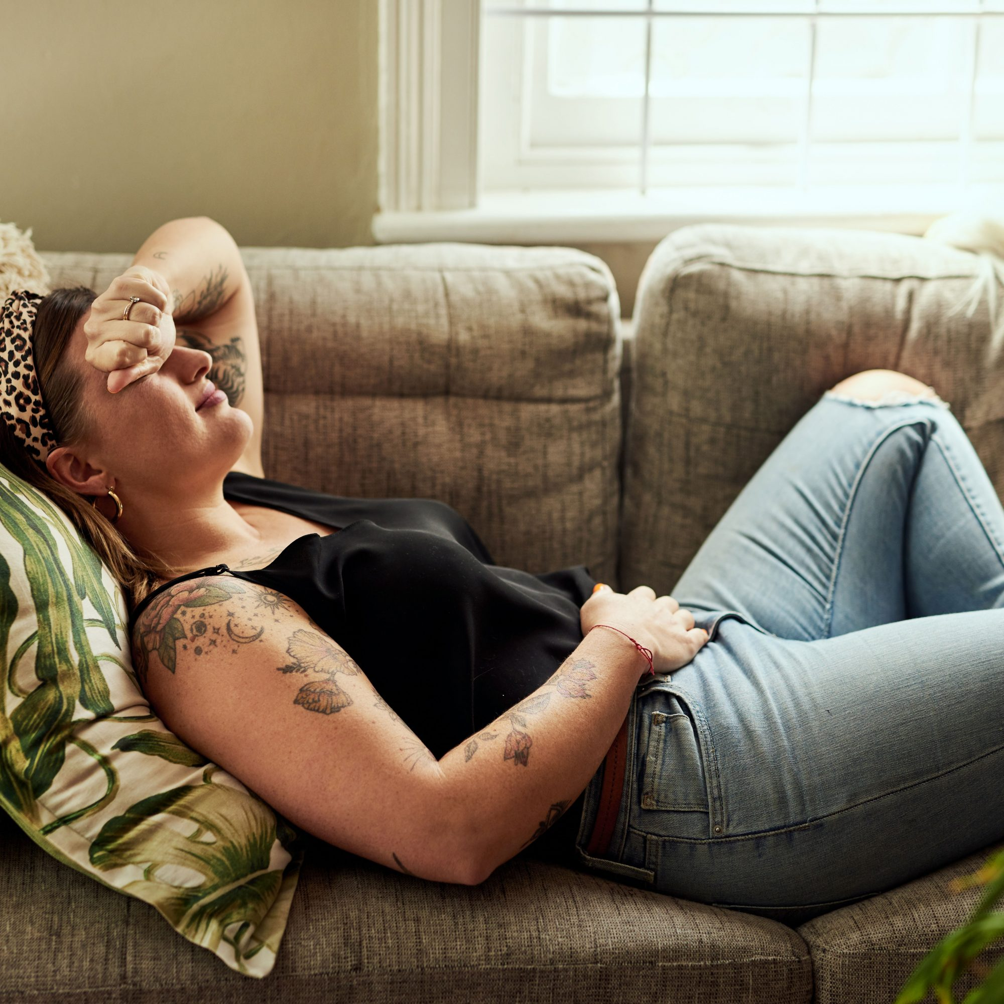 Woman_Laying_On_Couch_With_Hand_On_Abdomen