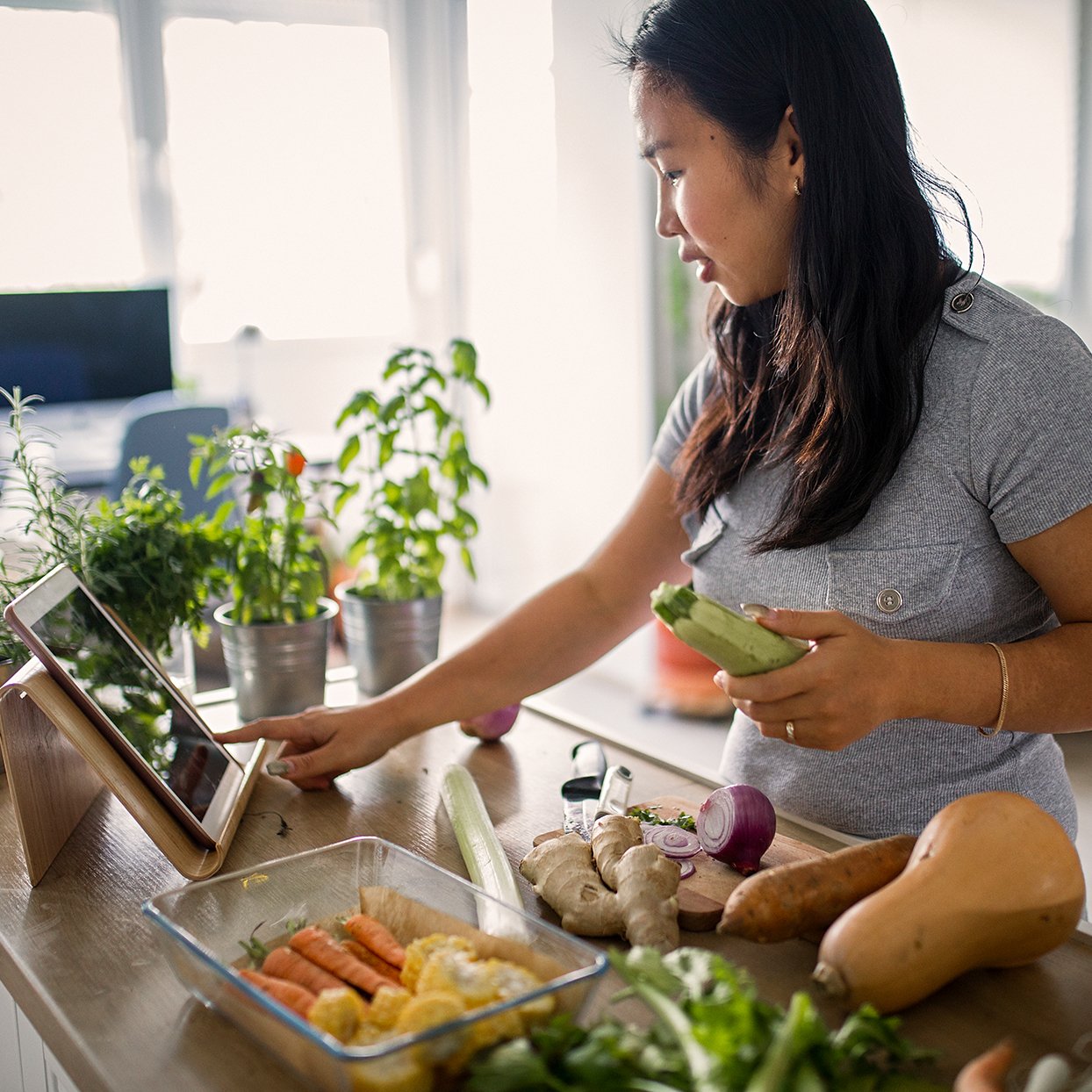 woman cooking dinner while looking at tablet