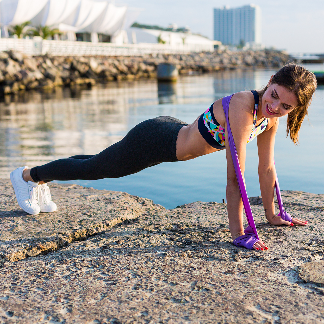 A woman performing a push-up as a resistance band chest exercise