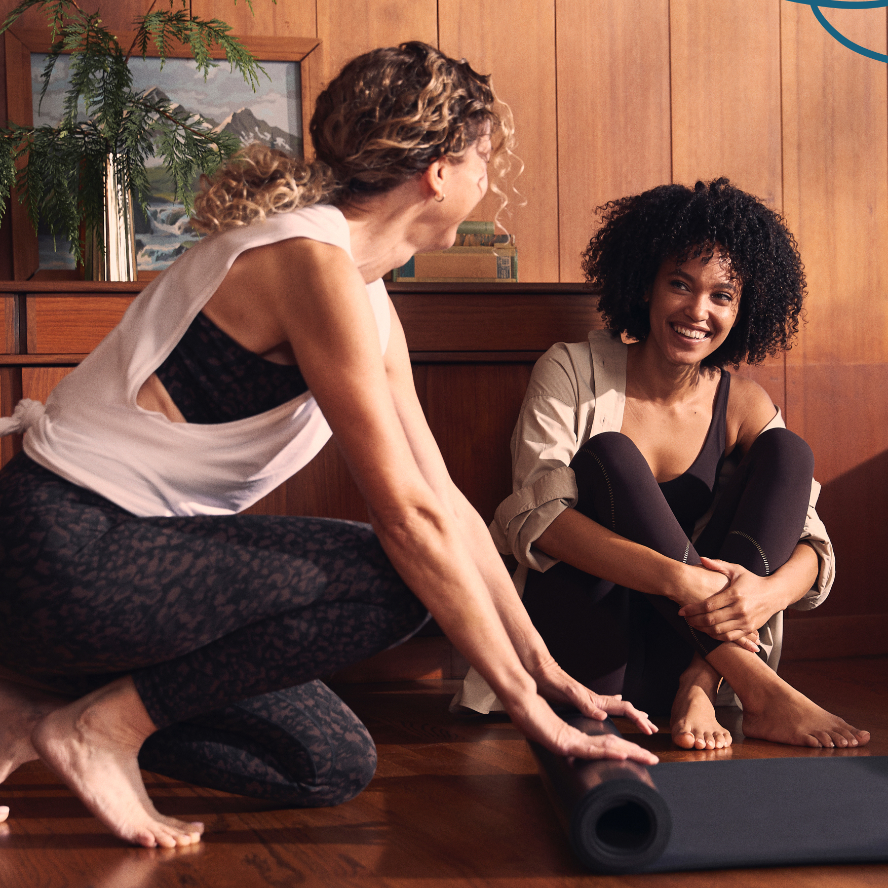 Two woman in lululemon activewear talking while stretching