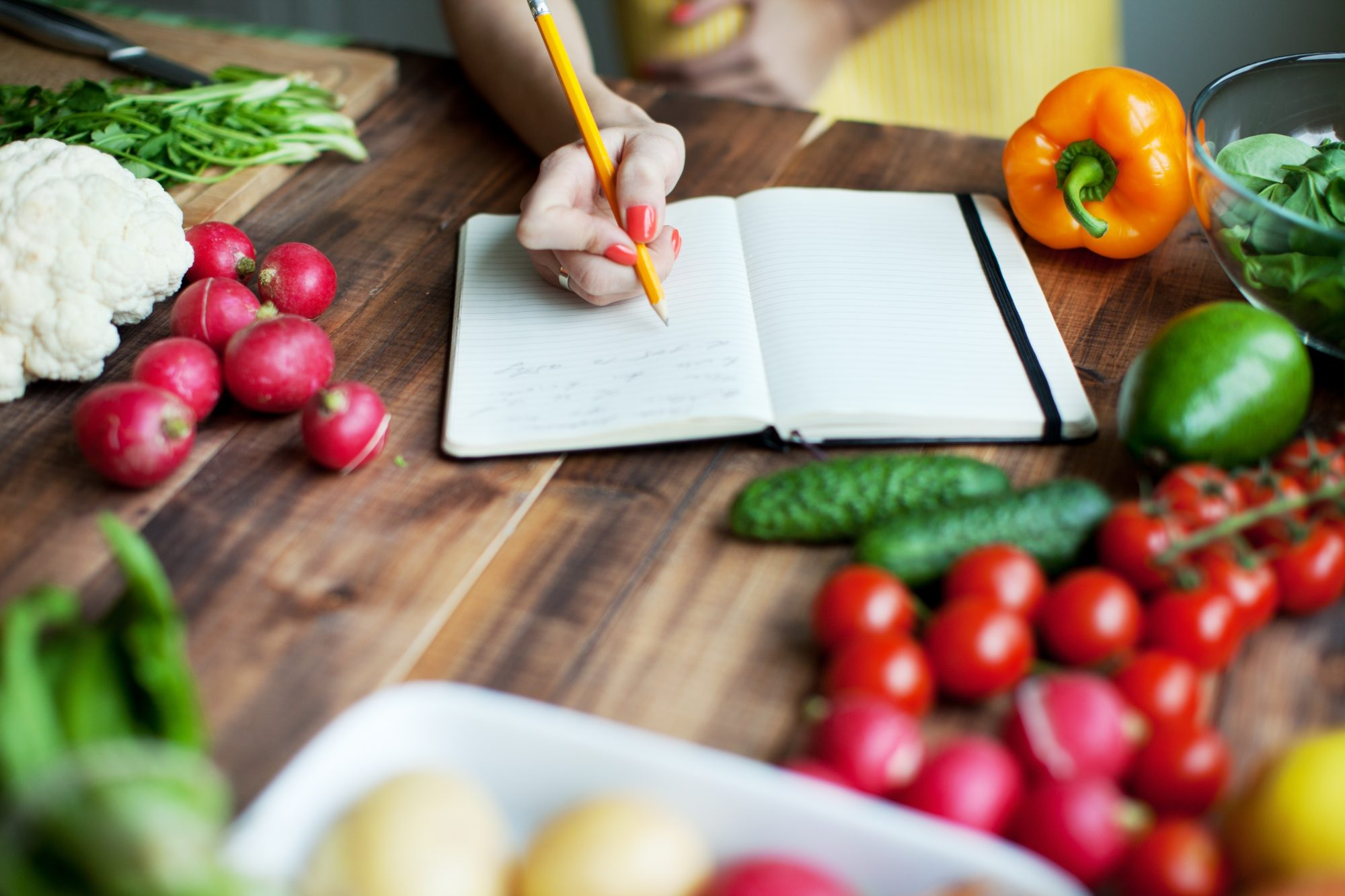 woman surrounded by healthy foods writing down dietary guidelines for americans 2020