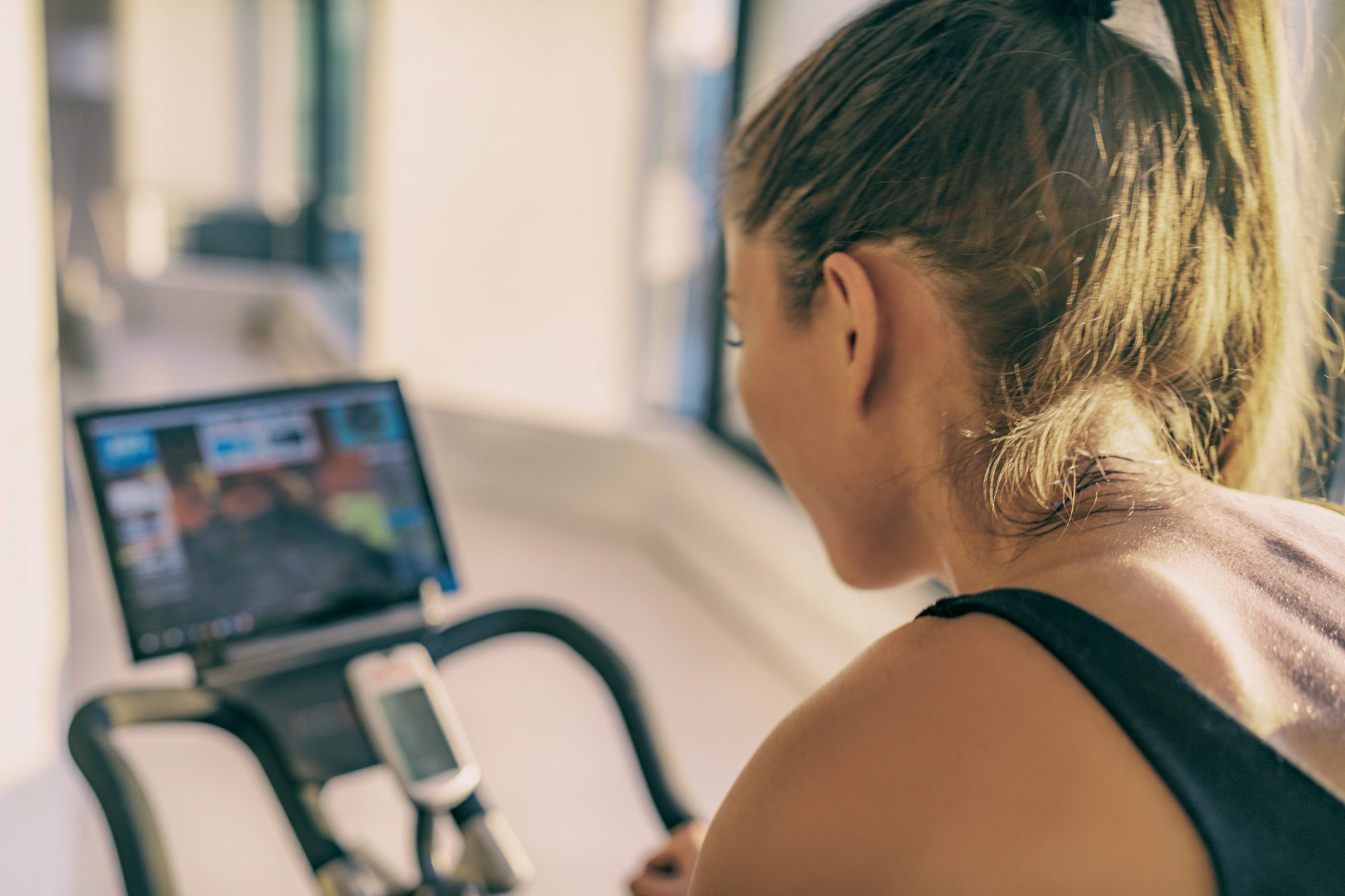 peloton bike alternatives , Smart fitness home workout biking screen with online classes woman training on stationary bike equipment indoors for biking exercise. Indoor cycling. Focus on the sweat on person's back.