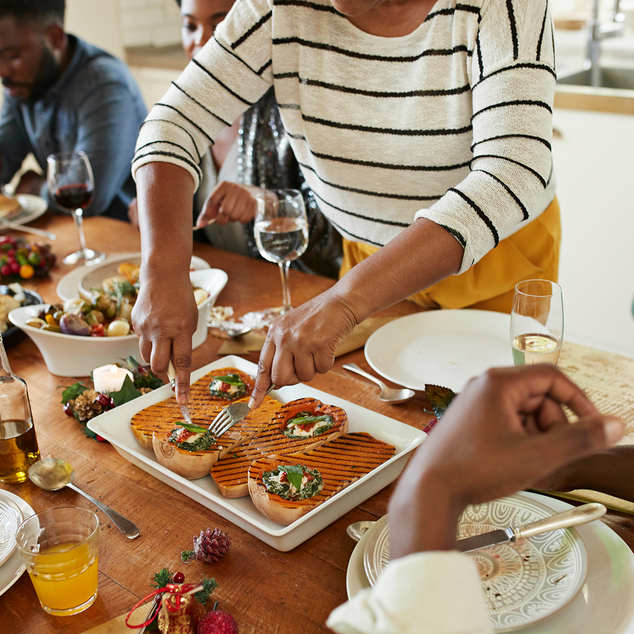 Midsection of woman serving appetizers to friends