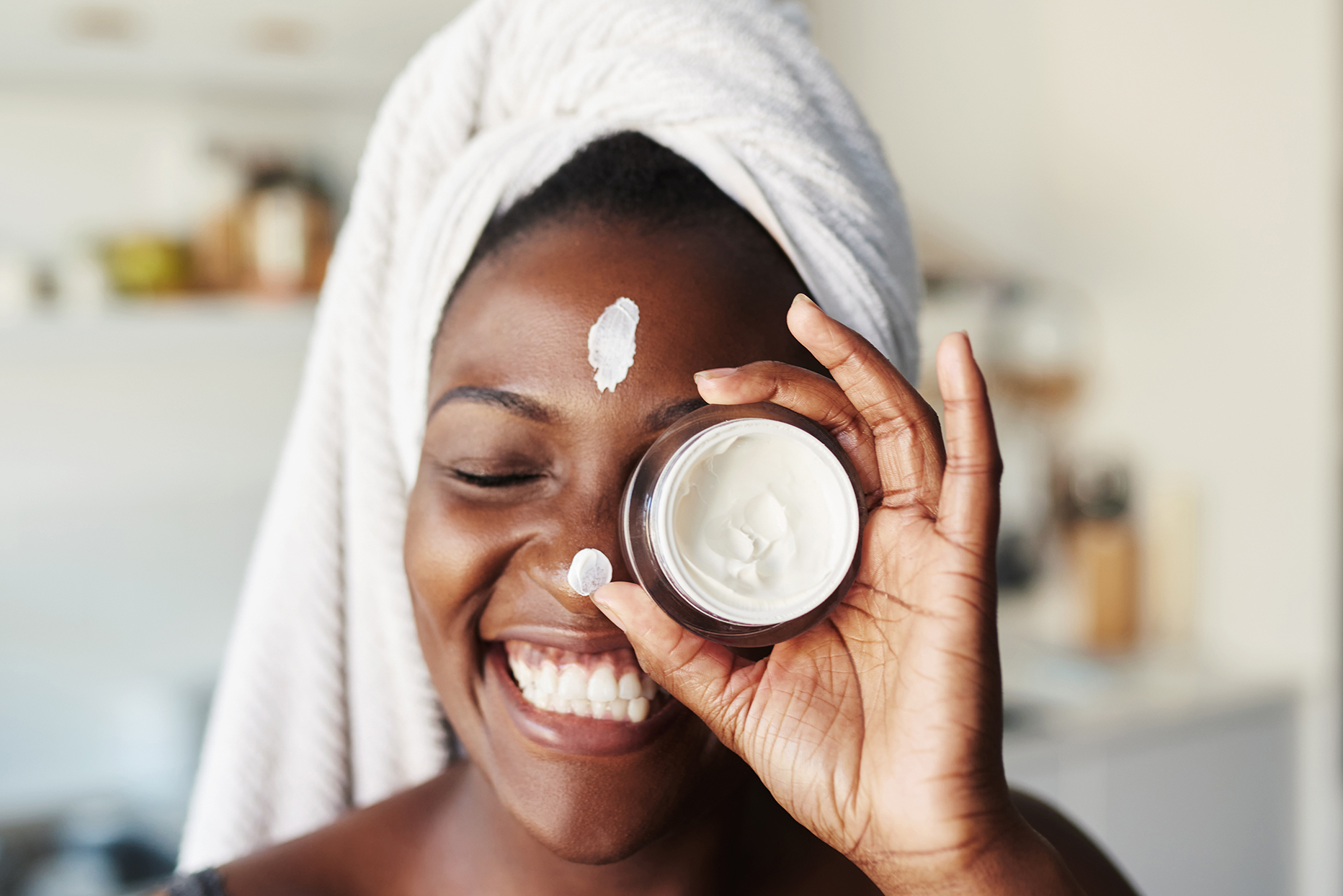 Woman with moisturizer on her face, holding a jar of lotion
