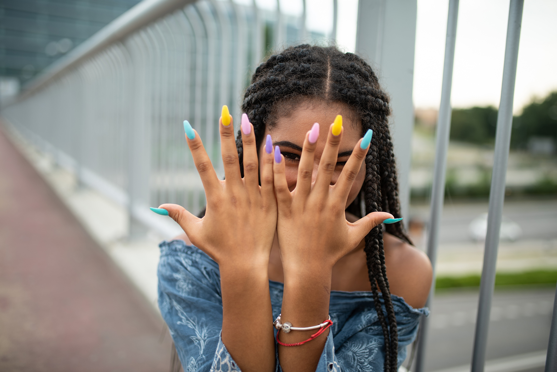 Model on city bridge posing with colorful nails