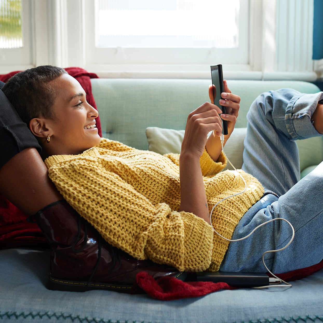 Woman messaging on phone while leaning on friend