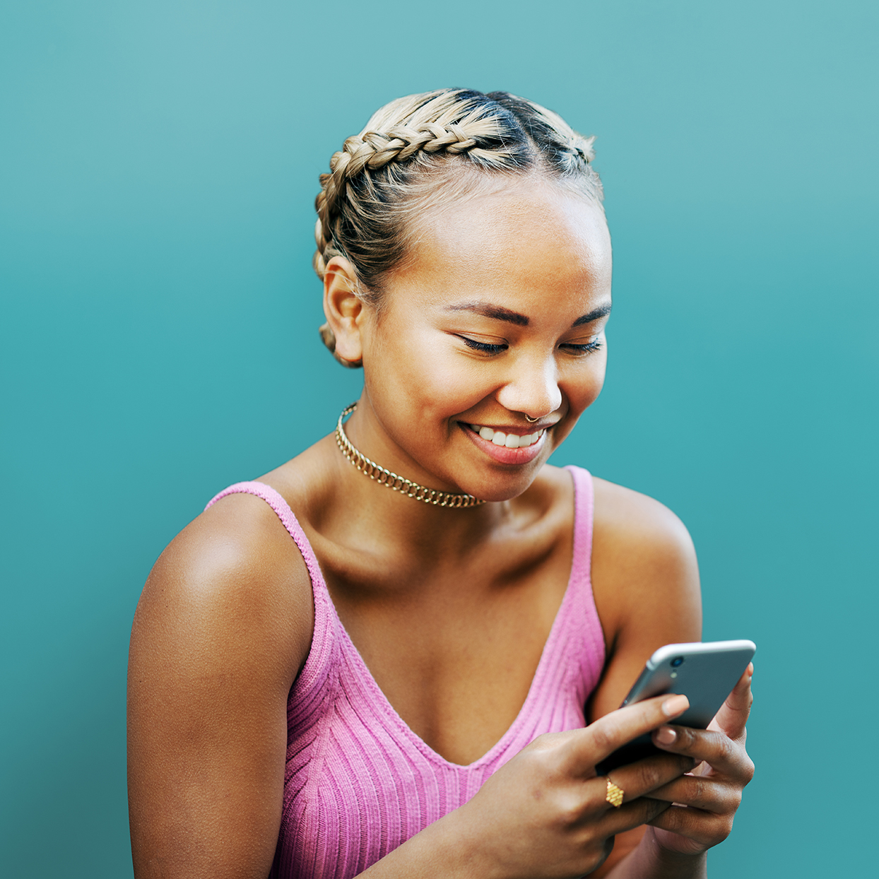 Woman smiling with smart phone, blue wall