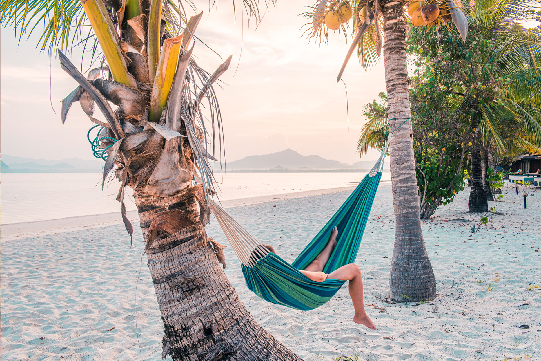 A woman laying in a hammock on a beach