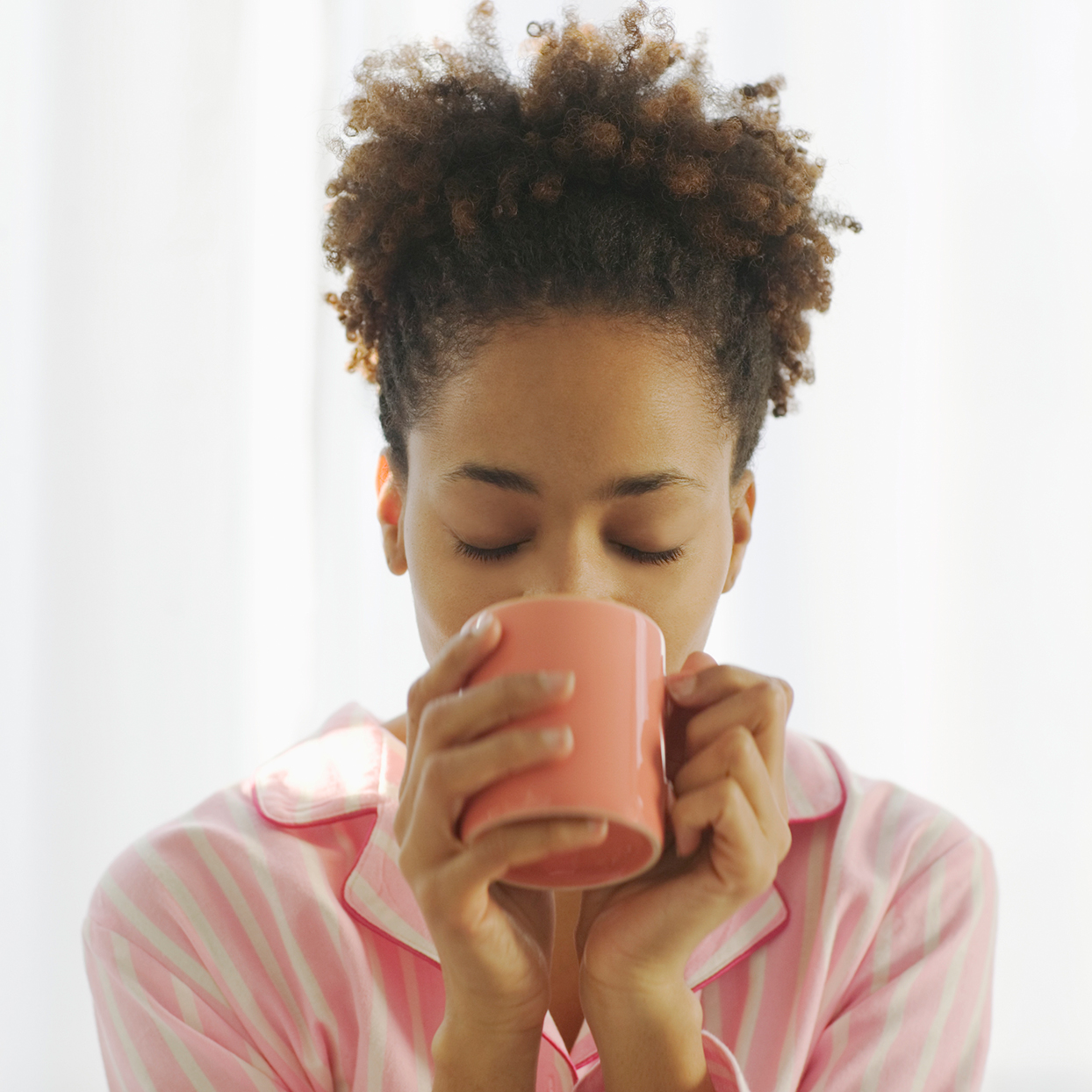 Young woman drinking hot beverage