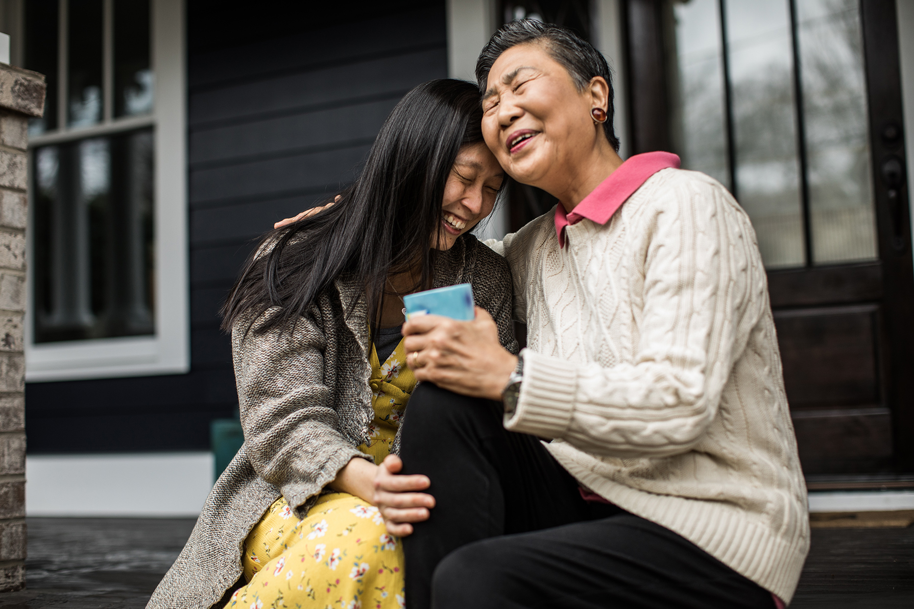Two Asian women hugging on a porch