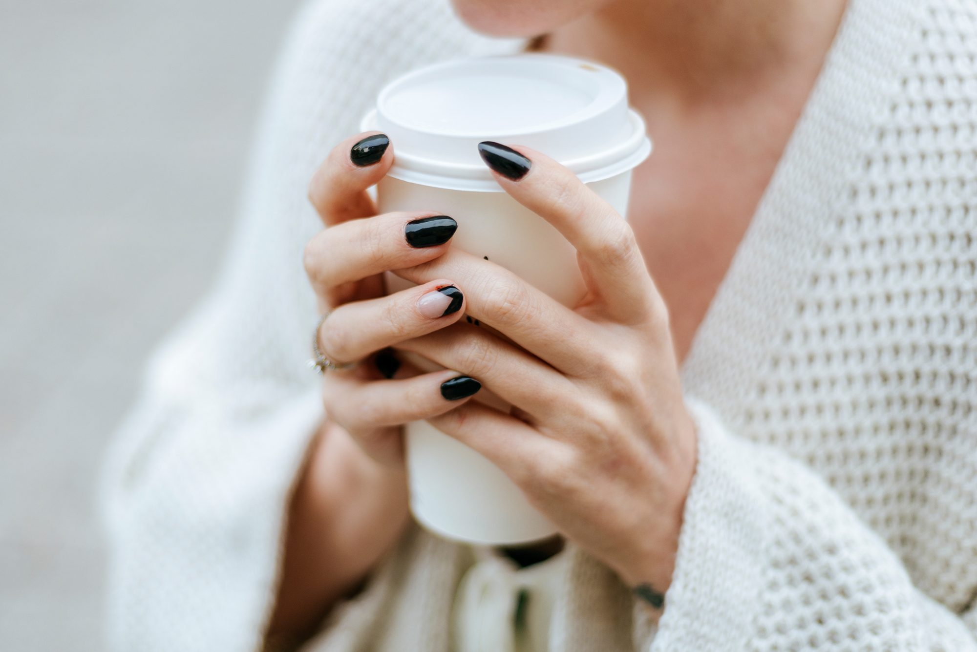 Close-up of woman's hands with take away drink