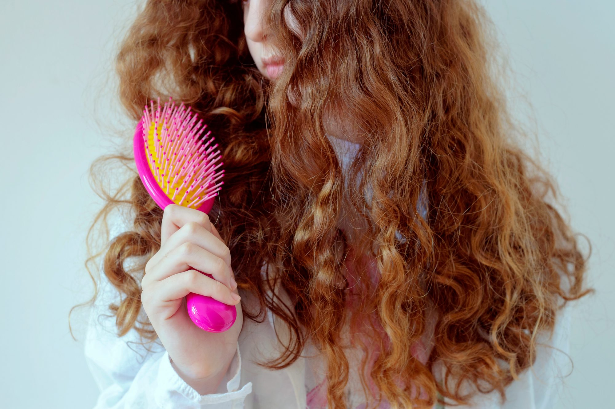 A woman brushing her red, curly hair