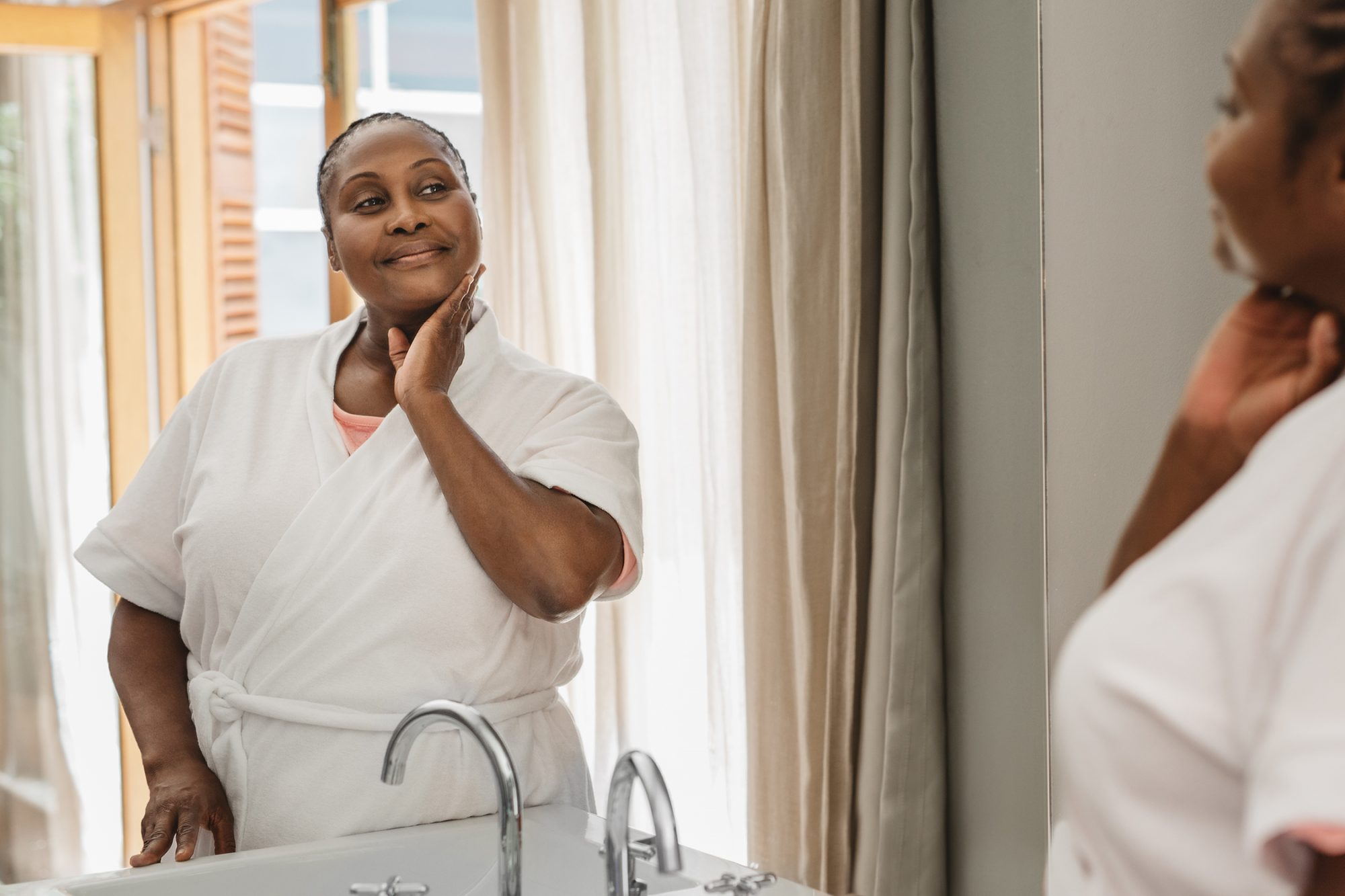 African American woman looking at her complexion in a bathroom