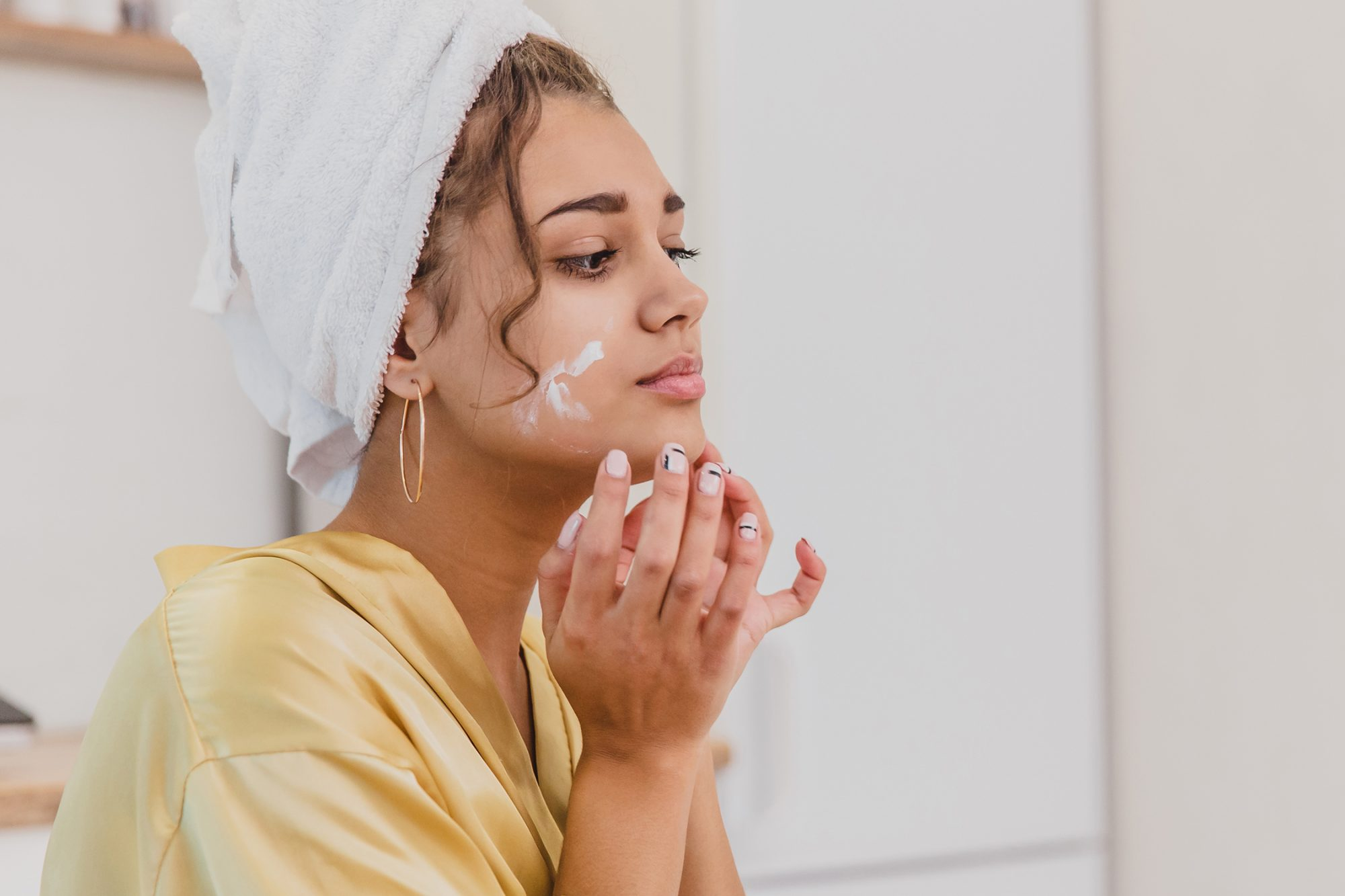 Beautiful, young woman wrapped in a towel spreading cream on her face. During this time it looks in the mirror. Calm