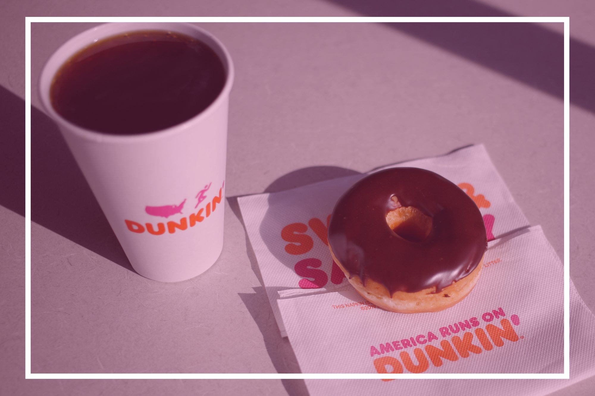 A black coffee and chocolate frosted donut are arranged for a photograph