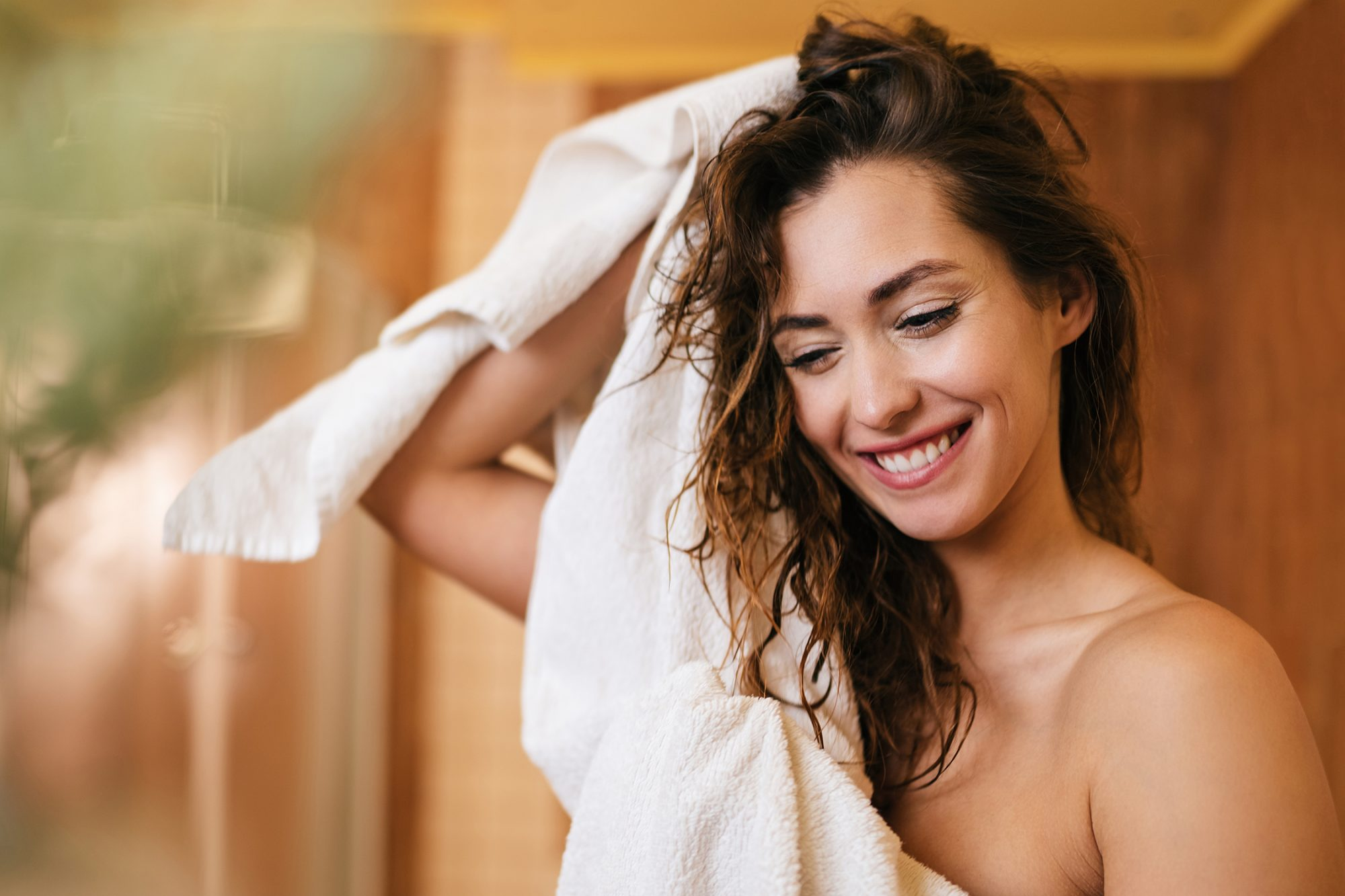Beautiful happy woman drying her hair with a towel in the bathroom.