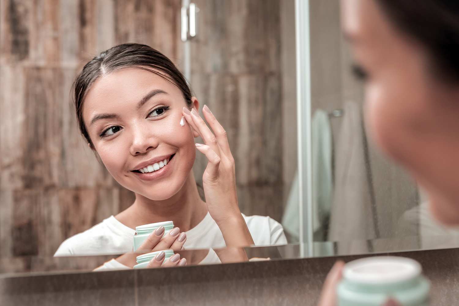 woman using face cream in the morning