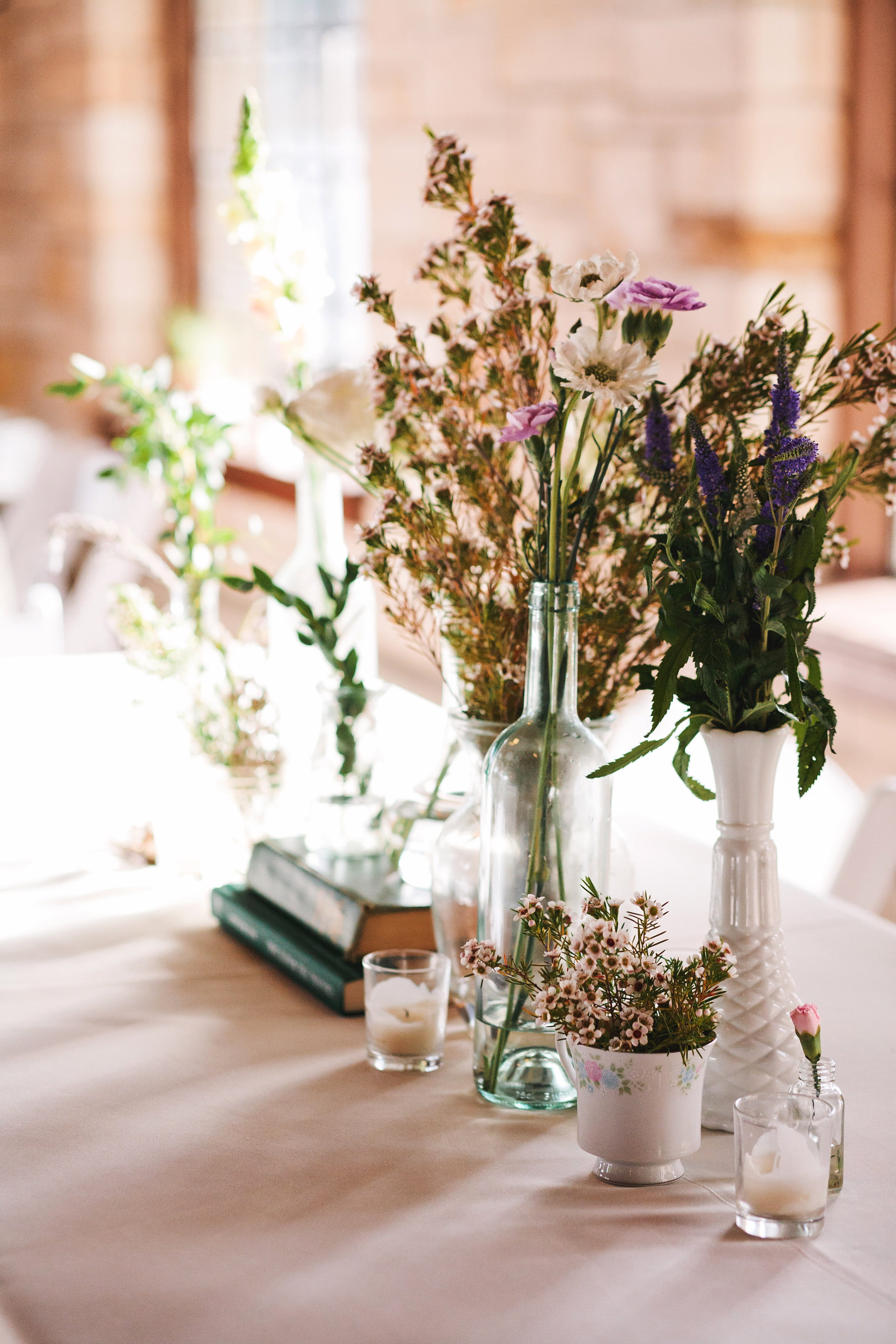 wedding centerpiece white vases candles purple flowers