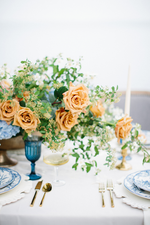centerpiece with orange garden roses and blue hydrangeas