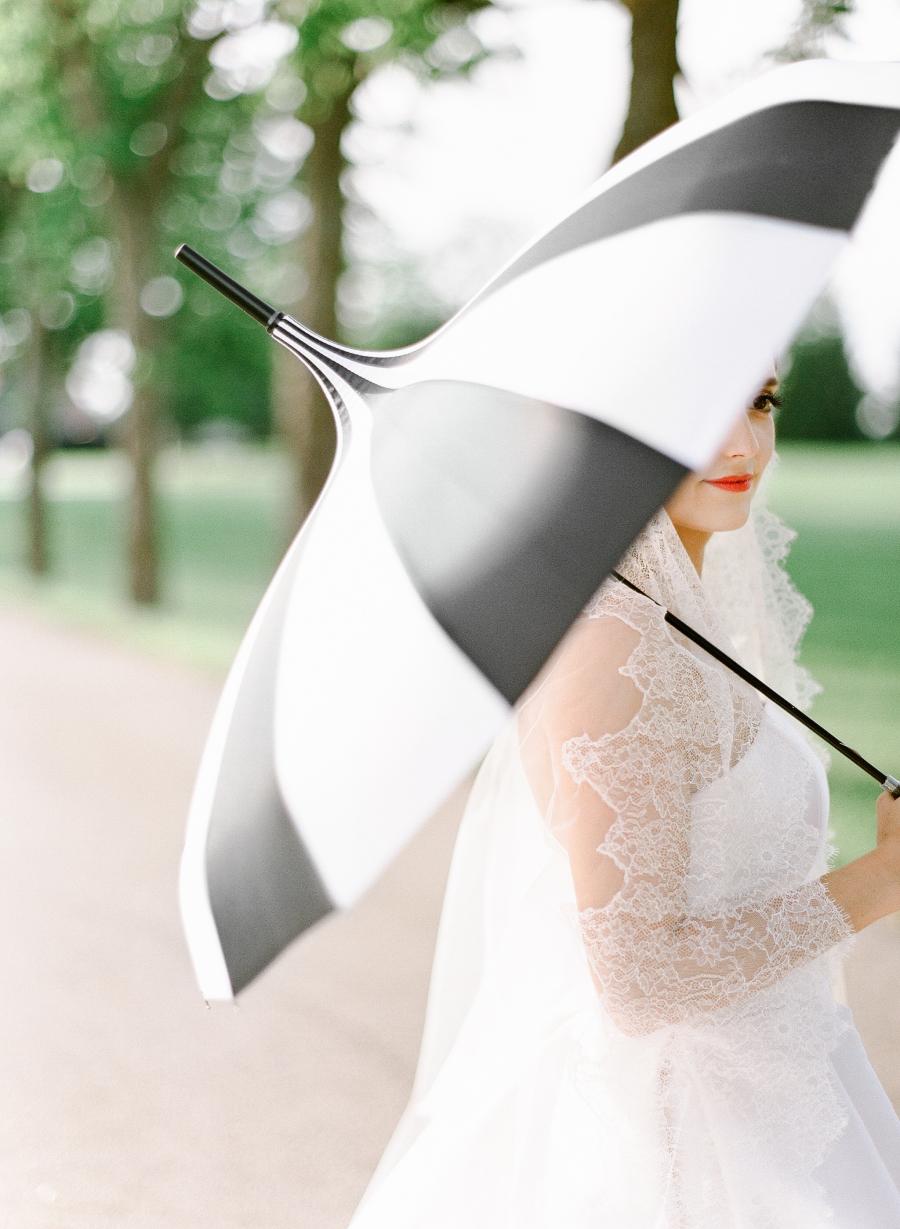 bride holding striped umbrella