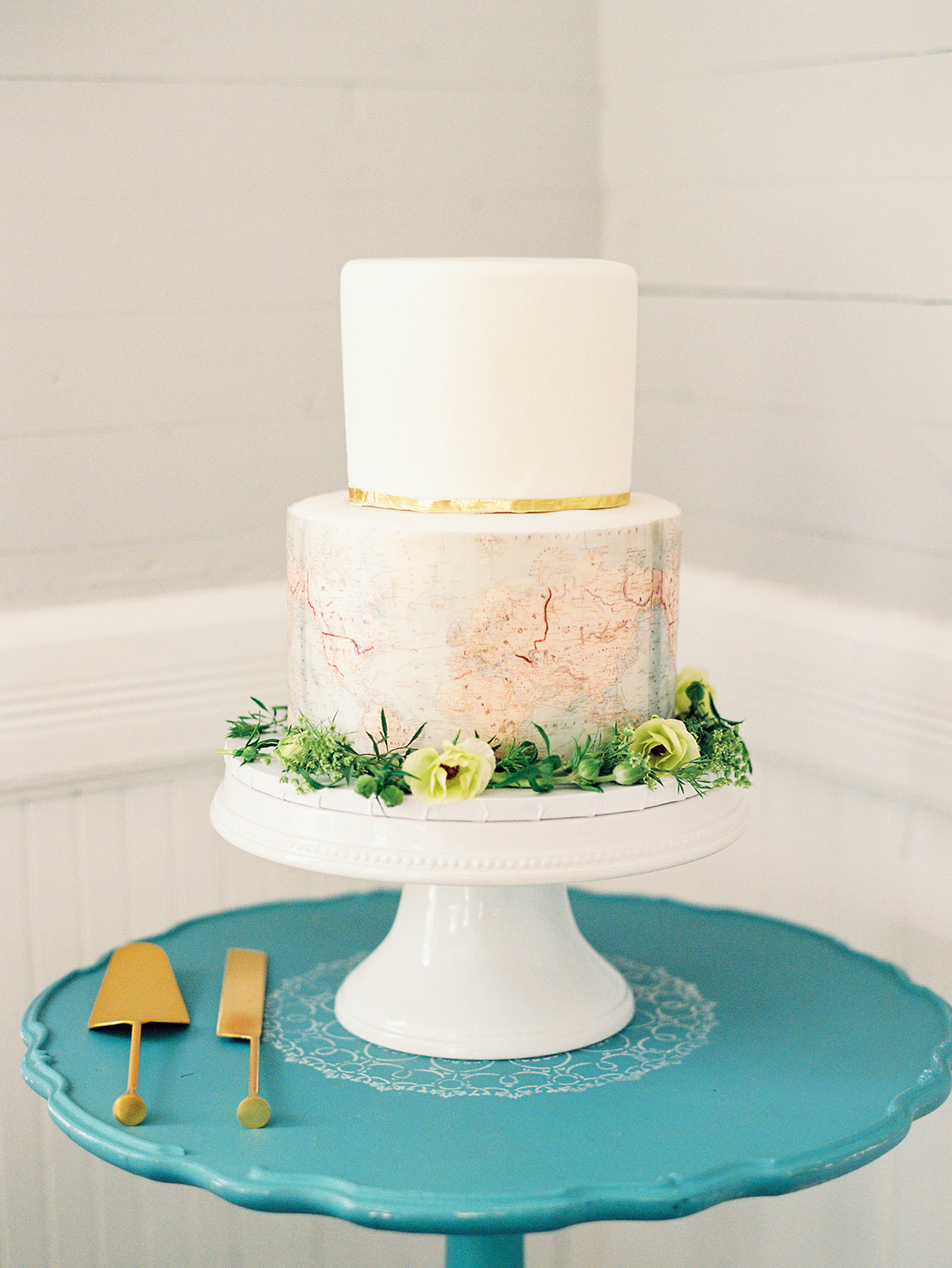 wedding cake with map design on the bottom tier