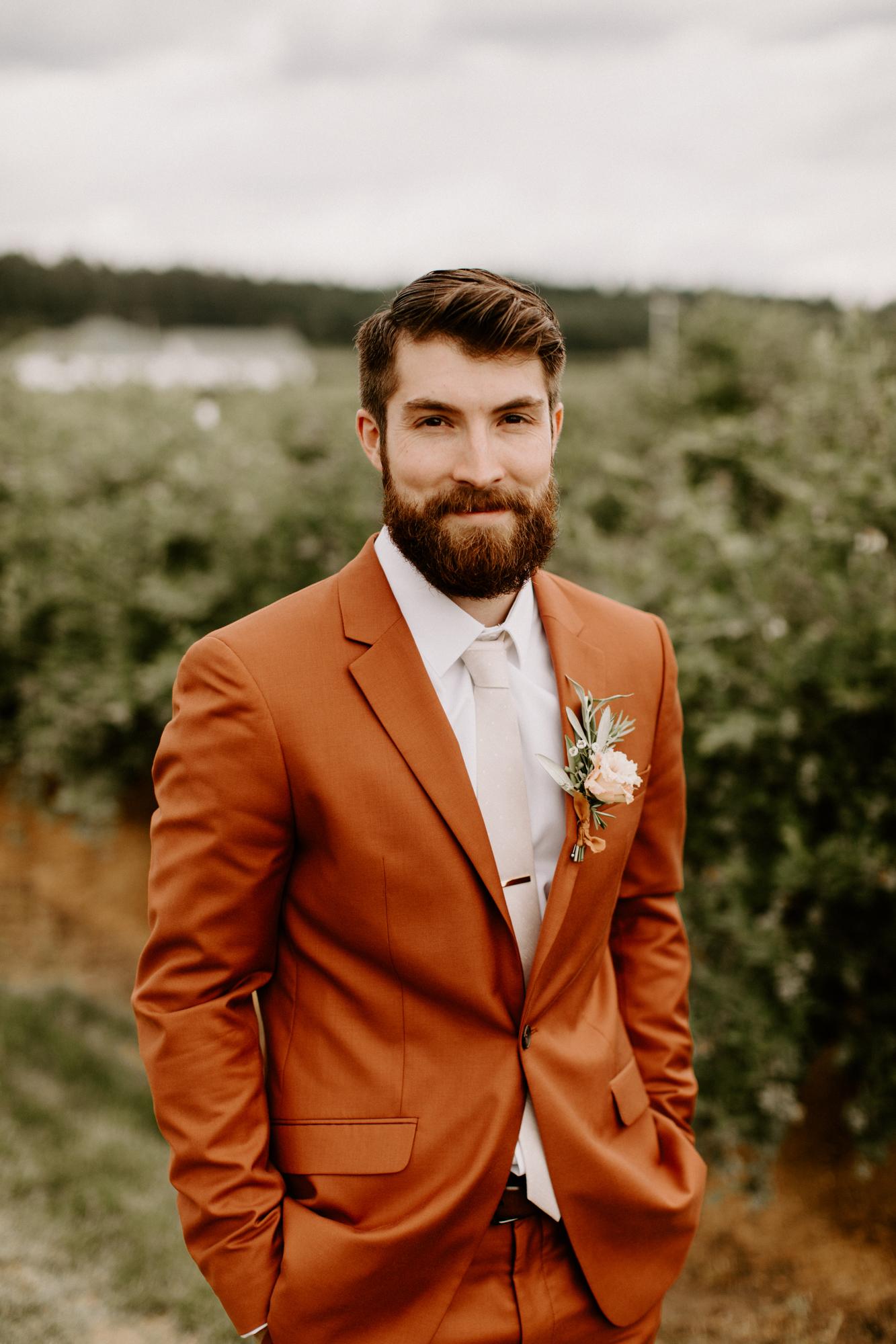groom in burnt orange wedding suit outside