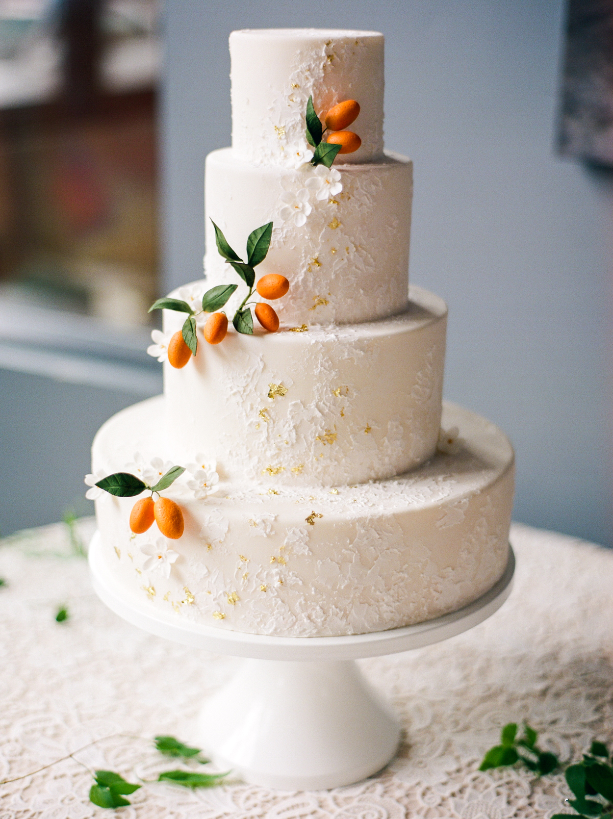 four tiered white wedding cake embellished with faux oranges