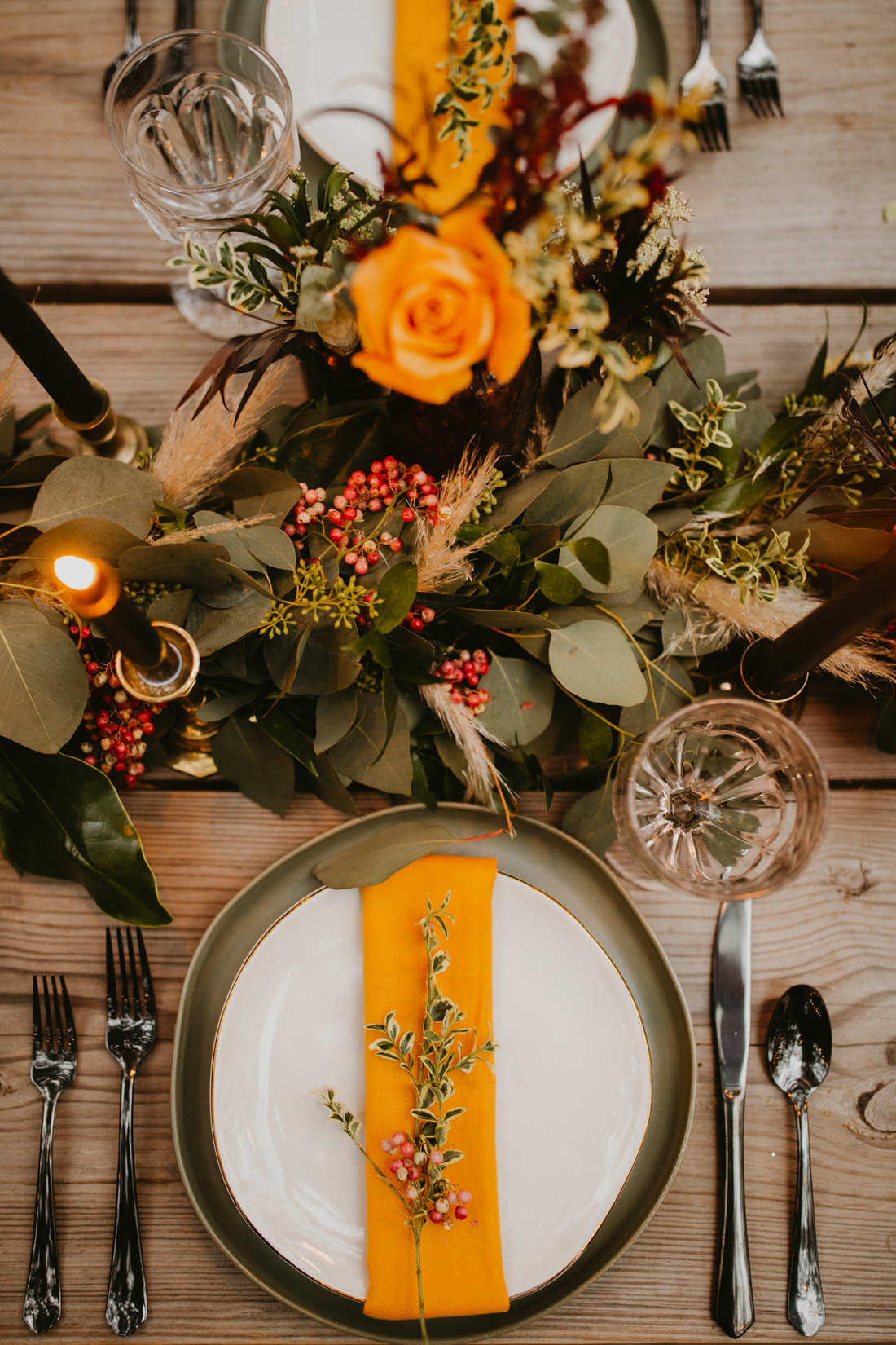 orange accented place setting with floral centerpiece