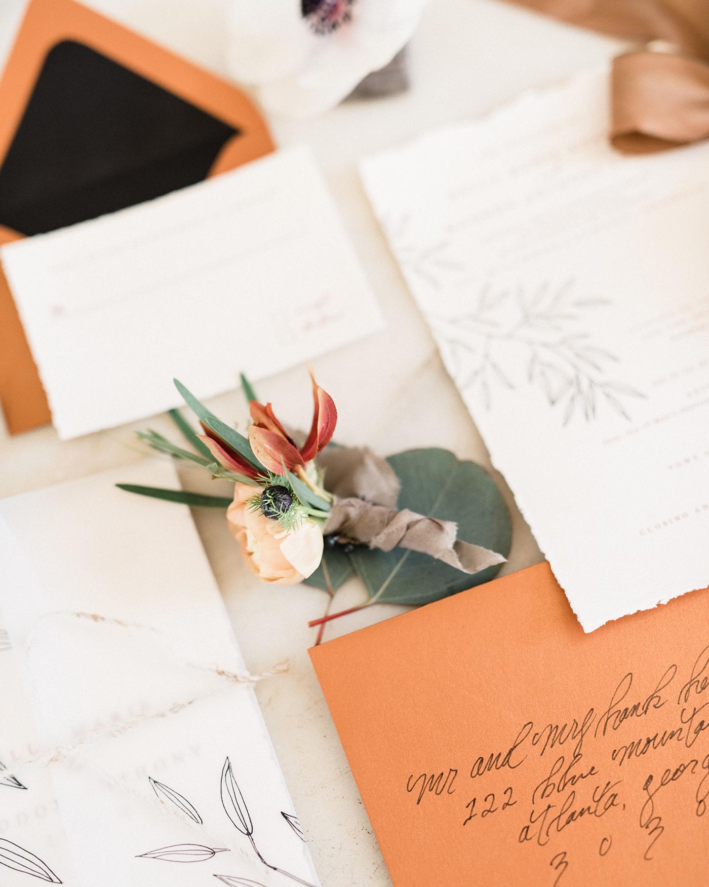 terra cotta decor envelopes and boutonnière