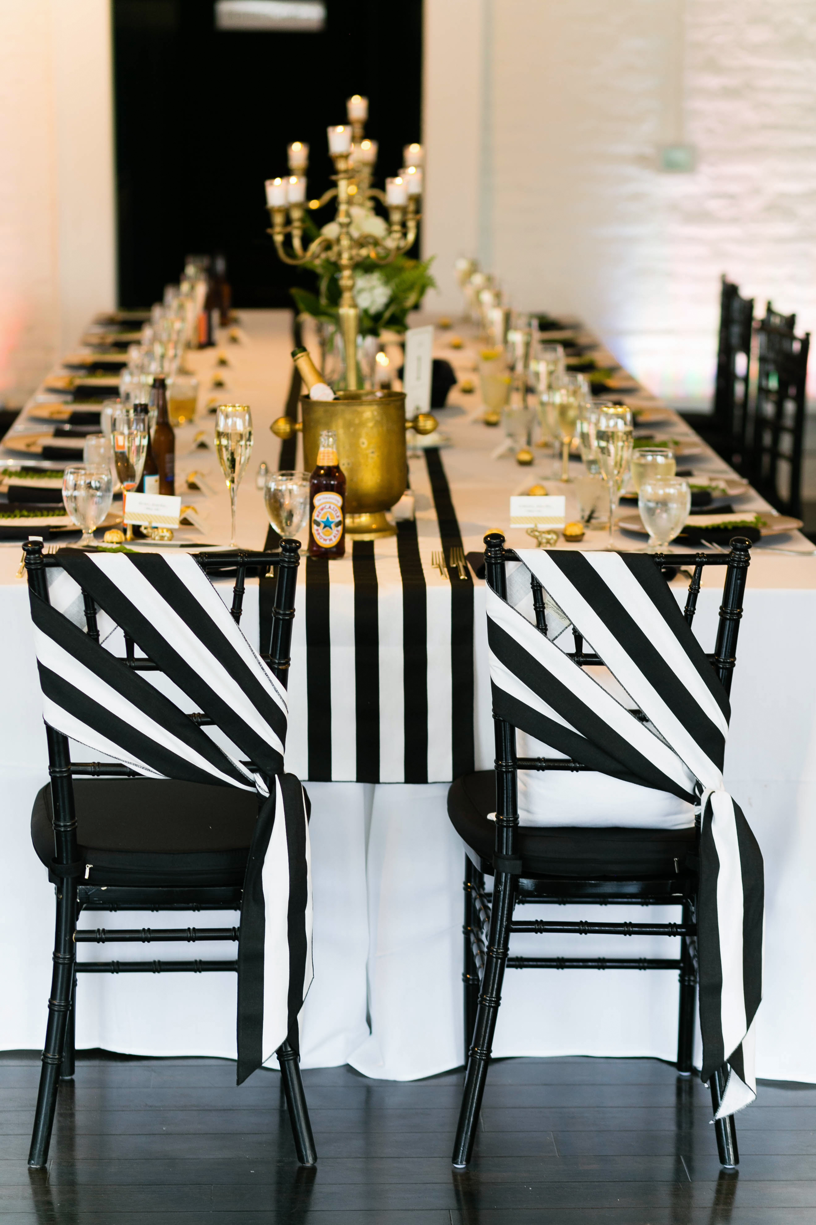 striped sashes on black chairs at reception table