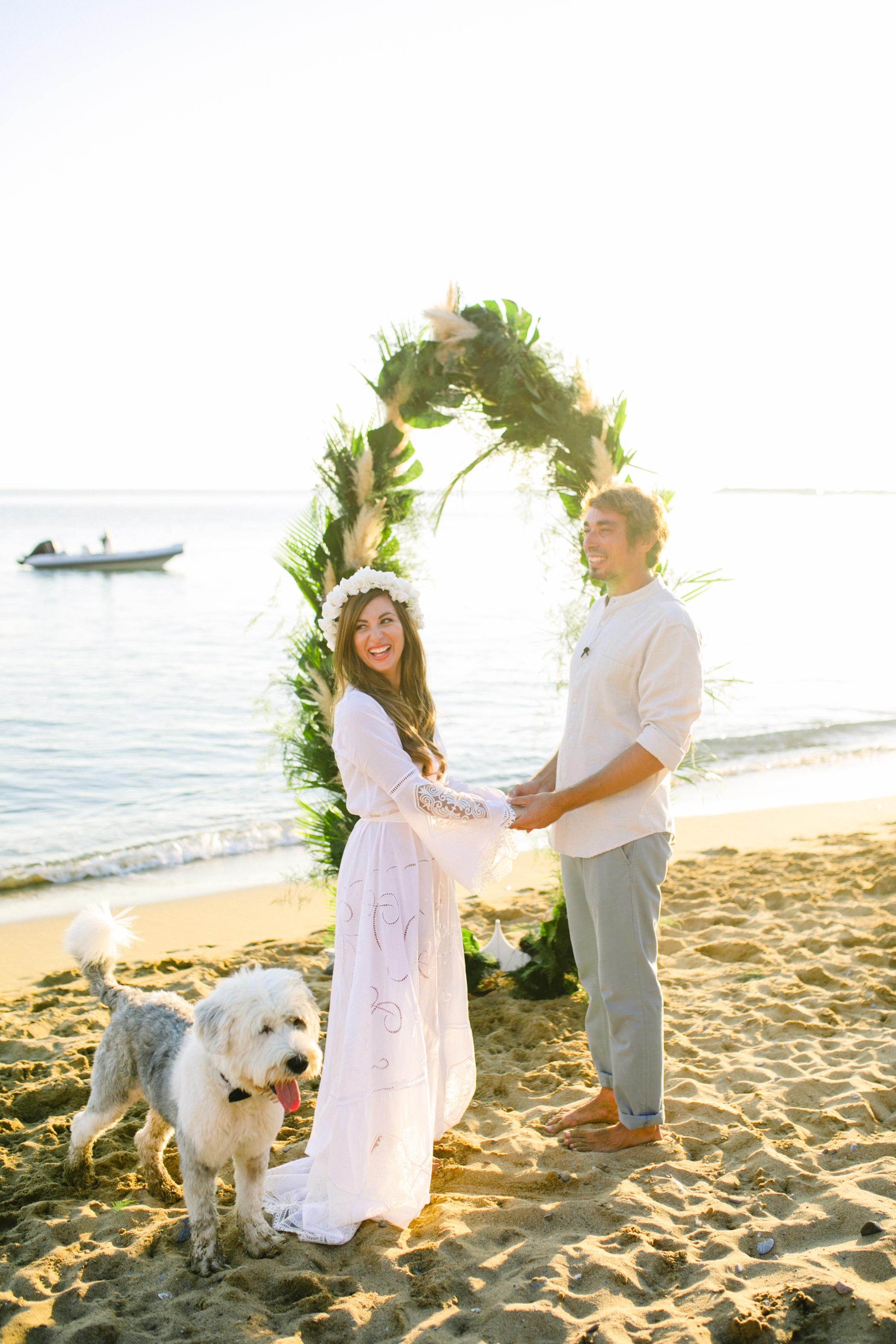 newlyweds with dog on beach
