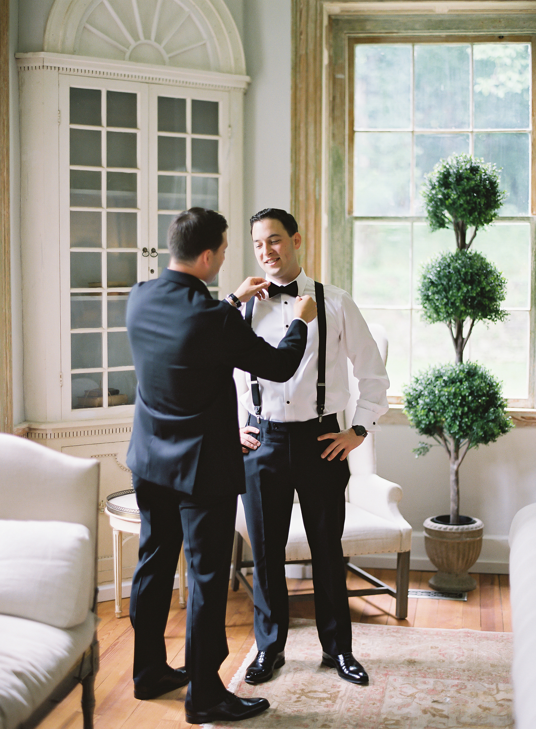 best man helping groom get ready