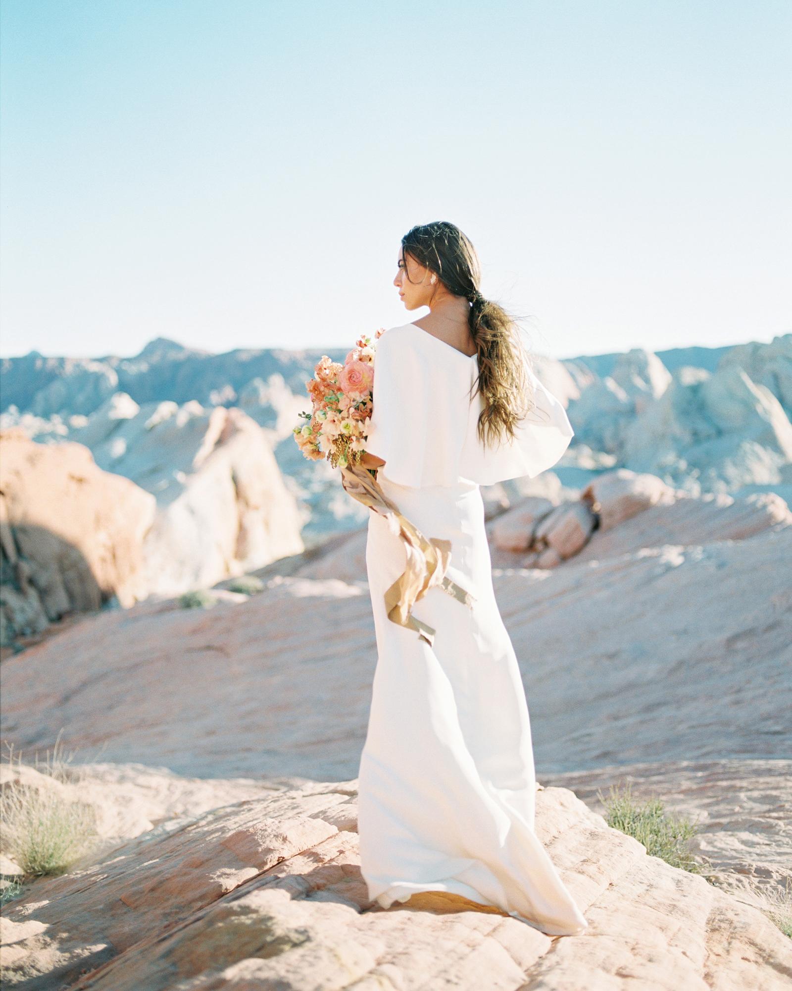 destination wedding dress standing on desert rocks
