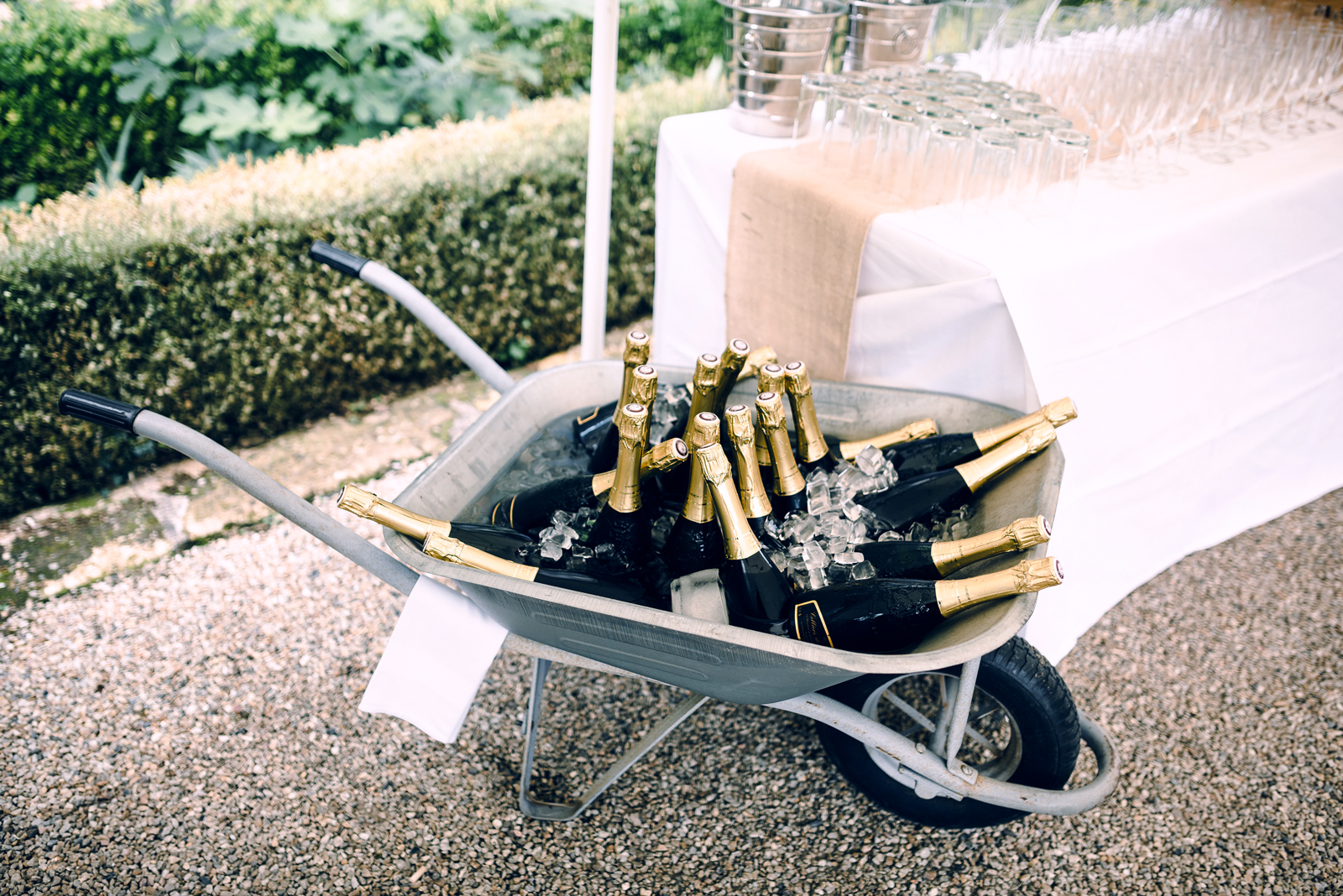 wheel barrow filled with ice and champagne bottles