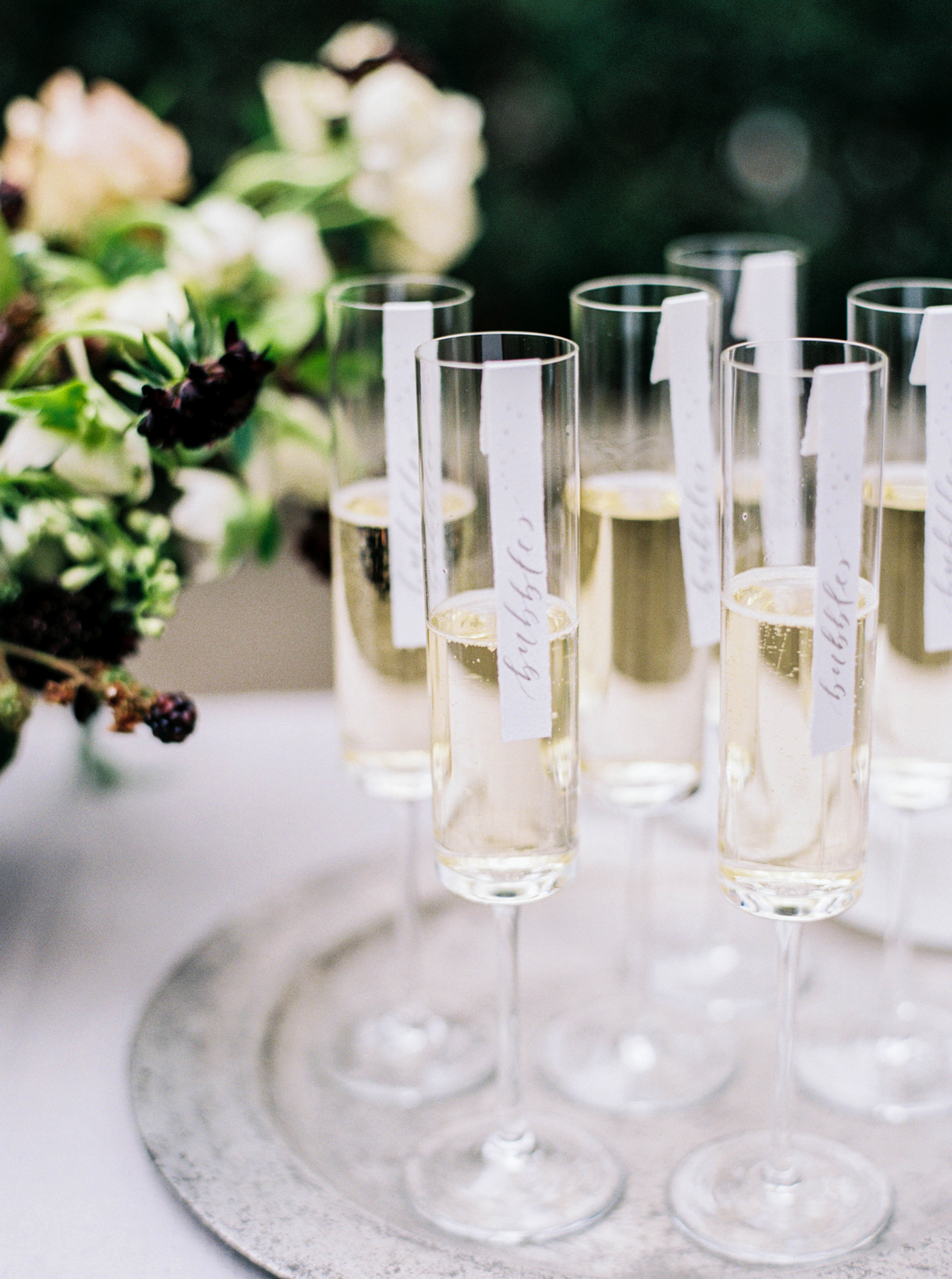 champagne flutes one silver serving tray with Calligraphed Labels