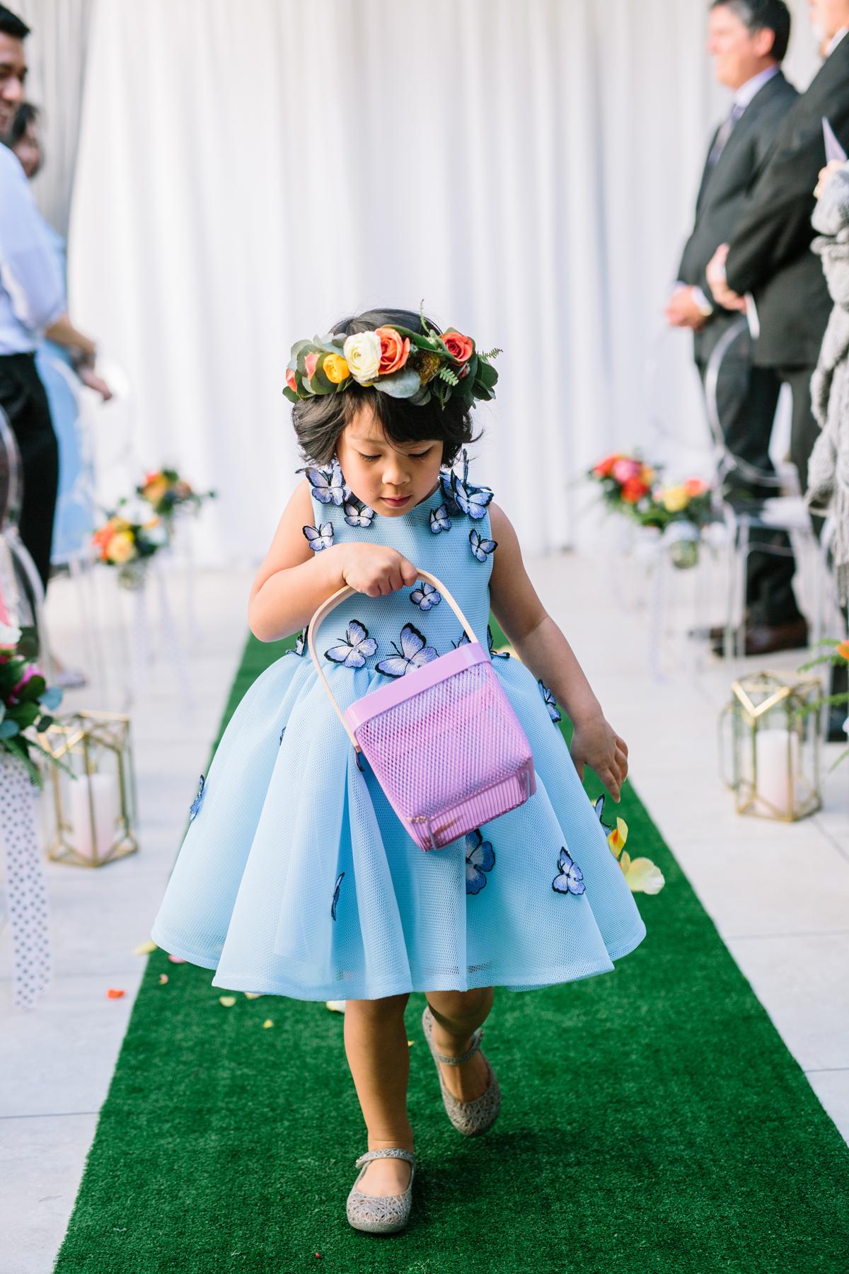 flower girl wearing blue dress with butterfly applique