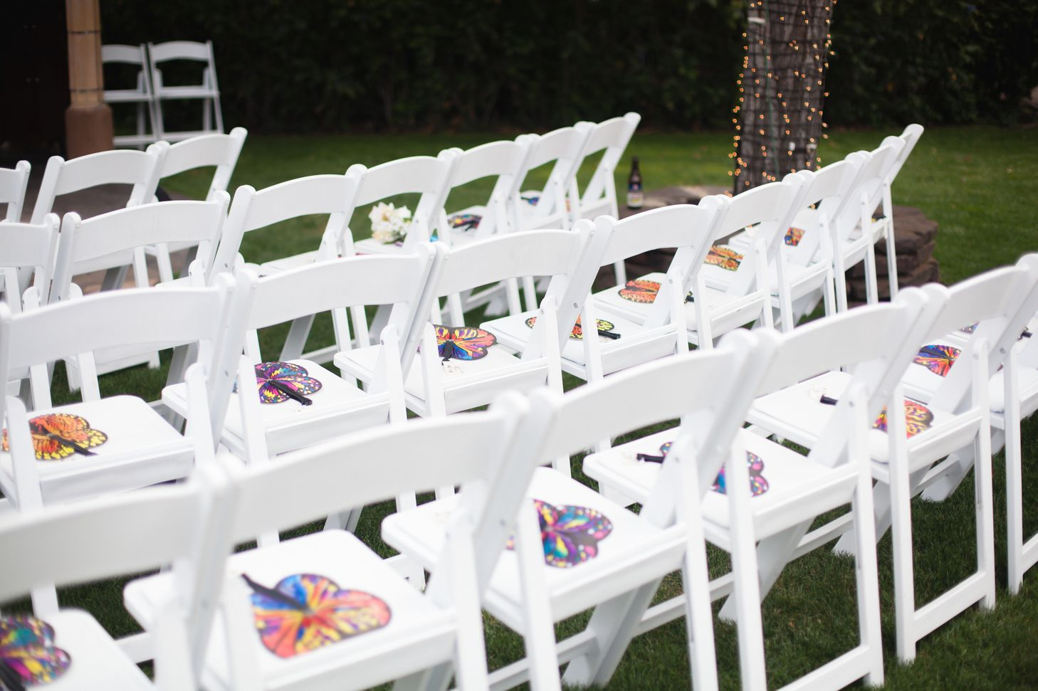 butterfly hand fans on white ceremony chairs
