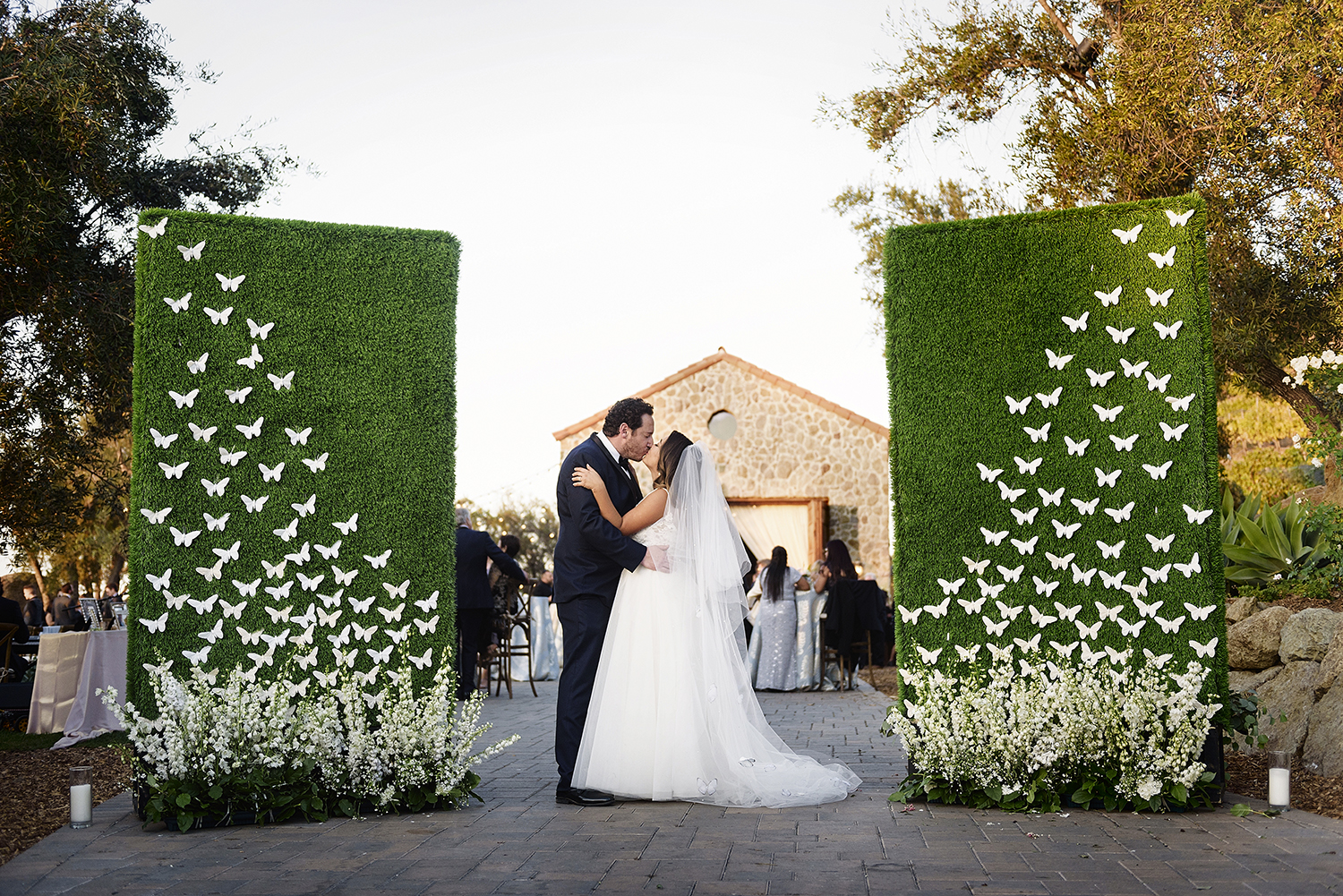 bride and groom kissing between hedges decorated with butterflies