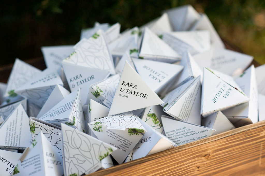 dainty white paper pyramid programs with black writing and greenery designs